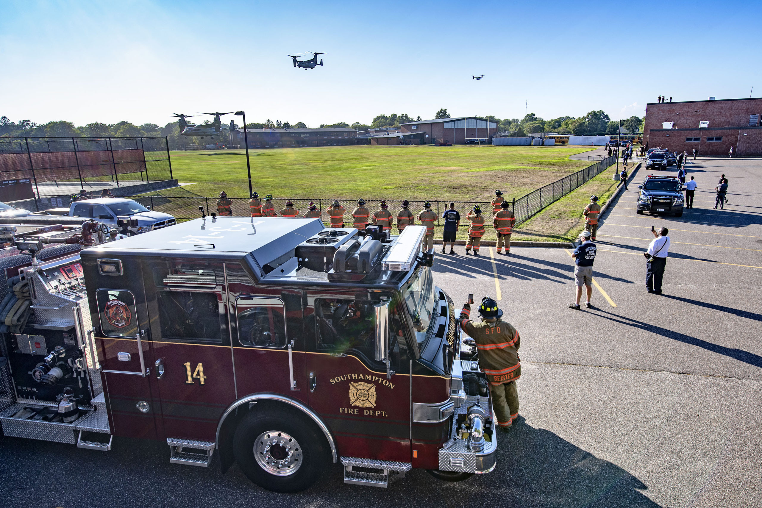 Members of the Southampton Fire Department look on as Marine Osprey aircraft carrying presidential staff come in for a landing at the athletic fields behind Southampton High School during President Trump's visit to the Hamptons on Saturday.    MICHAEL HELLER