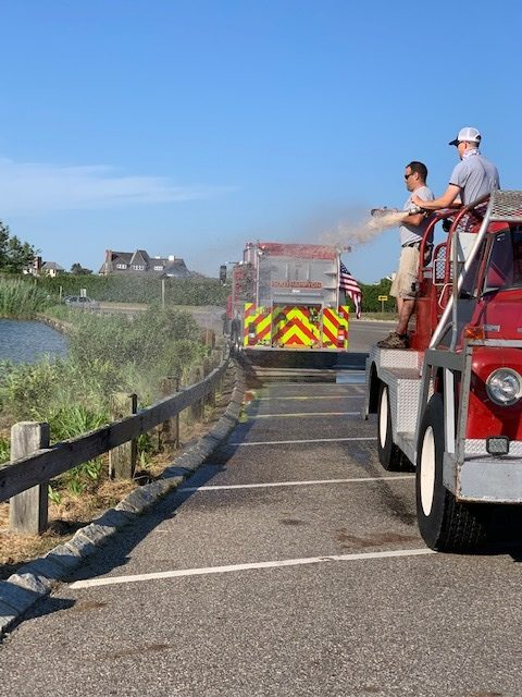 Members of the Southampton Fire Deparment have helped keep a newly planted bioswale at the foot of Lake Agawam moist during the hot, dry summer. COURTESY TONY PIAZZA