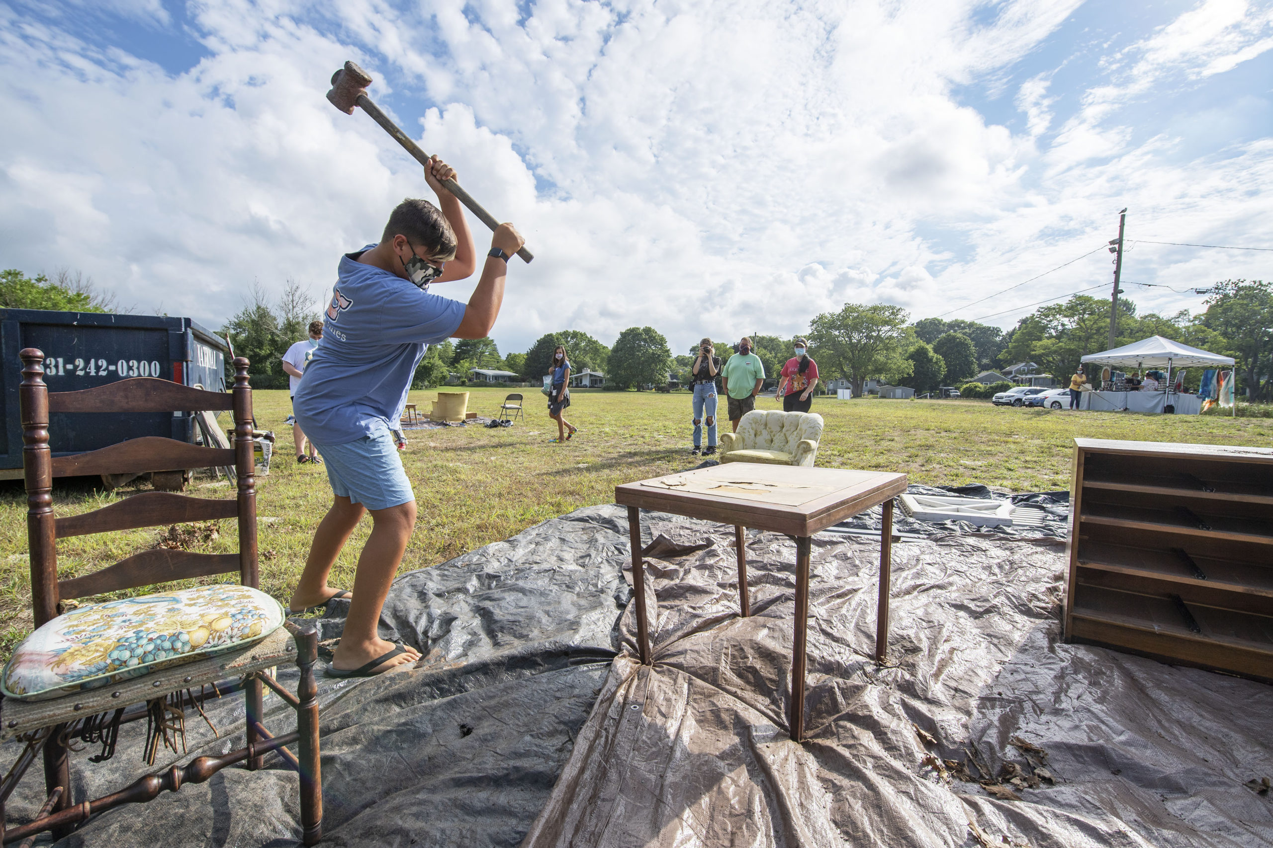 Cole Warren takes a sledgehammer to a card table during the Rage for Canines fundraiser that took place at Havens Beach on Friday evening.     MICHAEL HELLER