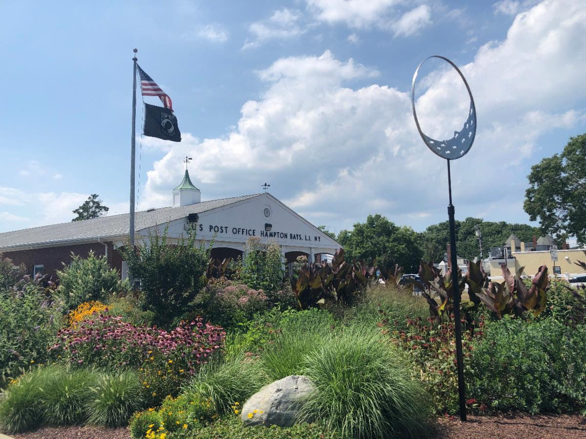 """The Hampton Bays Beautification Association is pleased to announce the installation of a steel art sculpture in the rain garden adjacent to the Hampton Bays Post Office. The sculpture, titled, """"Fish in a Crescent Moon,"""" was created by Hampton Bays artist Fritz Cass. Funding for the project was provided by the Muriel Siebert Foundation. COURTESY HAMPTON BAYS BEAUTIFICATION ASSOCIATION"""