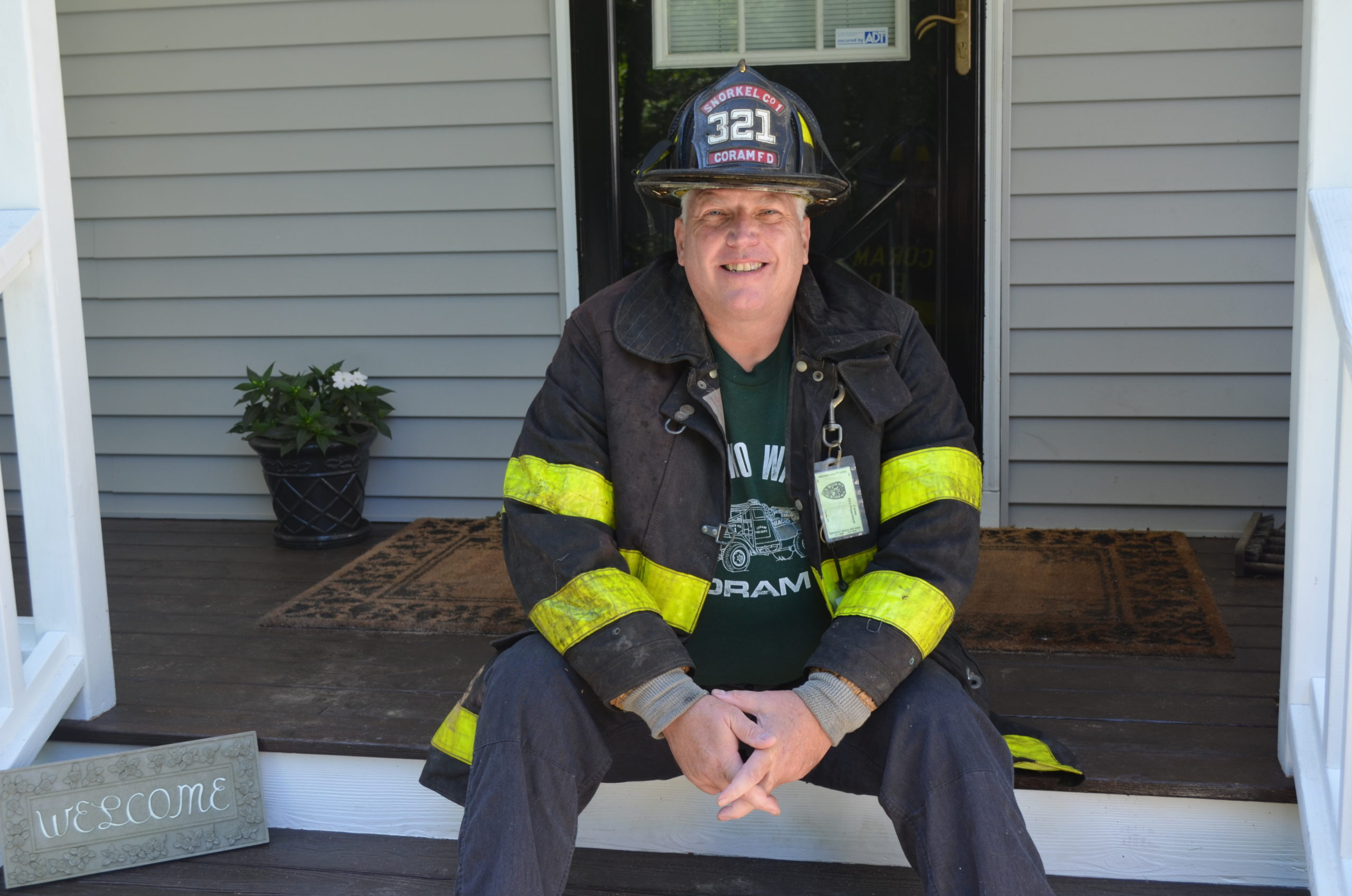 LJ Heming in his turnout coat and helmet on the front porch of his home in Hampton Bays.