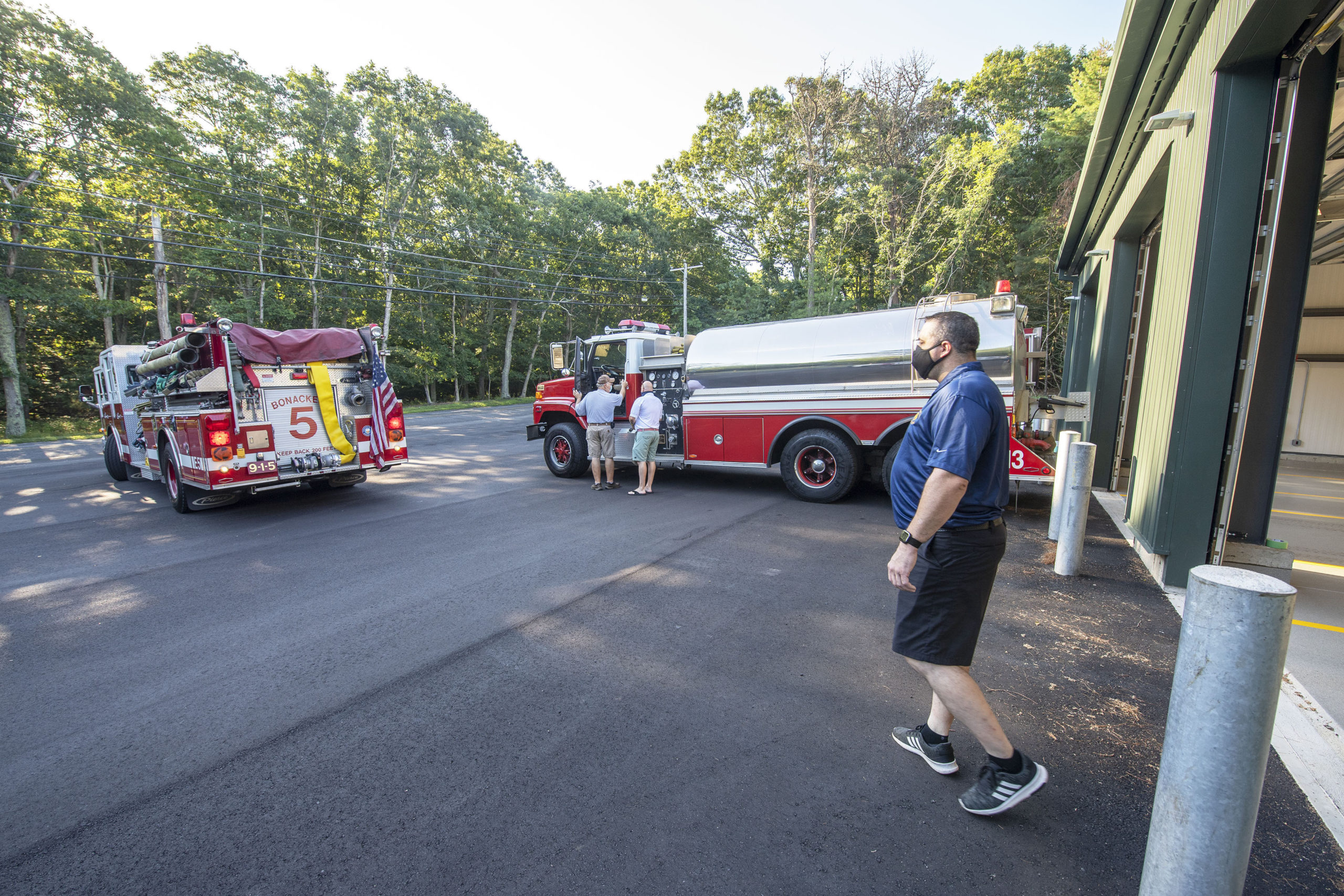 East Hampton Fire Department First Assistant Chief Duane Forrester helps guide Engine 9-1-5 into place as East Hampton Fire Department trucks 9-1-5, 9-1-10 and 9-1-13 are moved into the brand new EHFD Substation on Old Northwest Road on Saturday.   MICHAEL HELLER