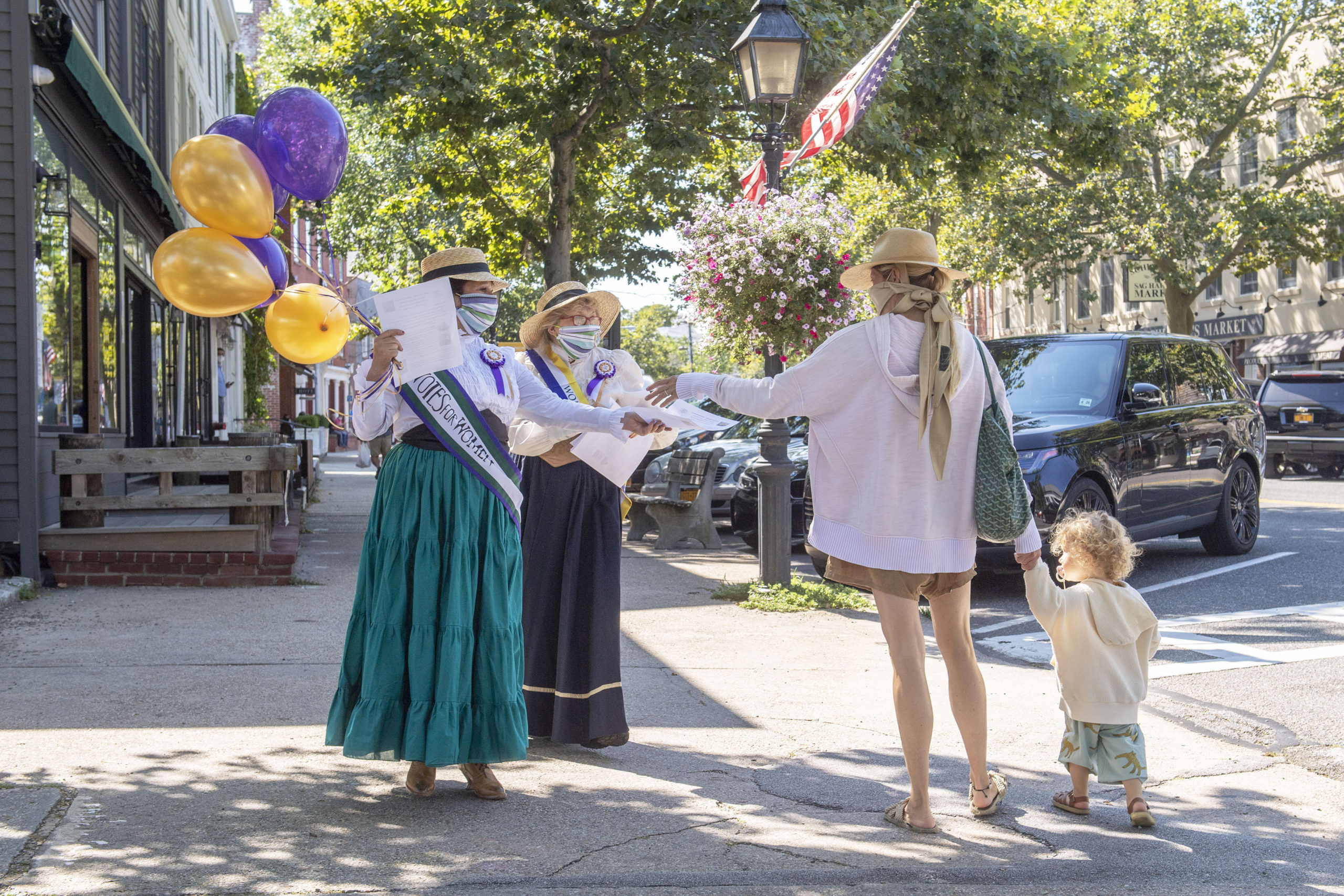 To honor the 100th anniversary of the 19th Amendment and women's right to vote, WLNG radio personality Bonnie Grice and Christ Episcopal Church Pastor Karen Campbell, in conjunction with the Sag Harbor Historical Society, wear period outfits and hand out fliers on Main Street in Sag Harbor on August 26. MICHAEL HELLER