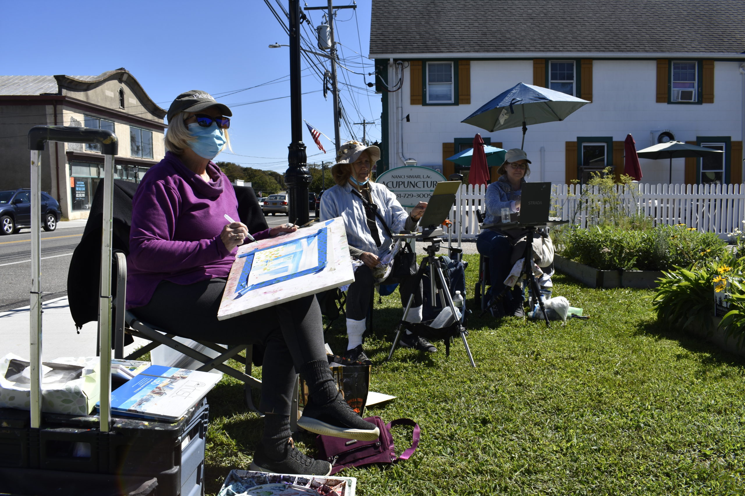 Plein air artists Susan Bracken Gilday, Laurie Schlageter and Laurie Spellman paint on Main Street.