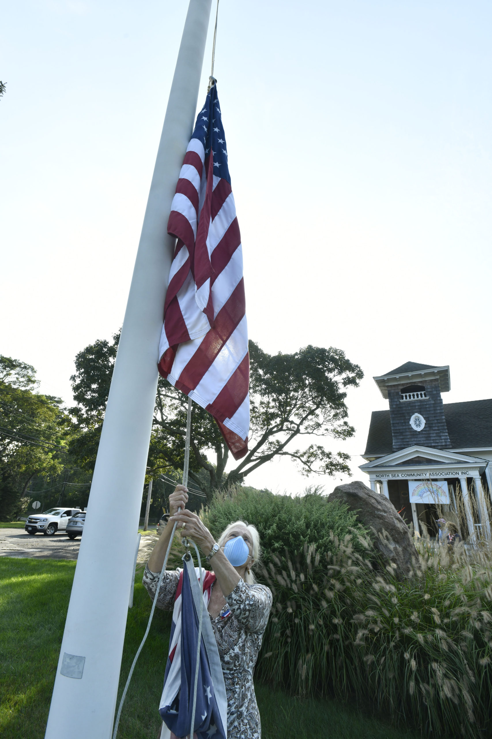 Barbara Fair lowers the flag to half-staff on Friday morning at the North Sea Community House.