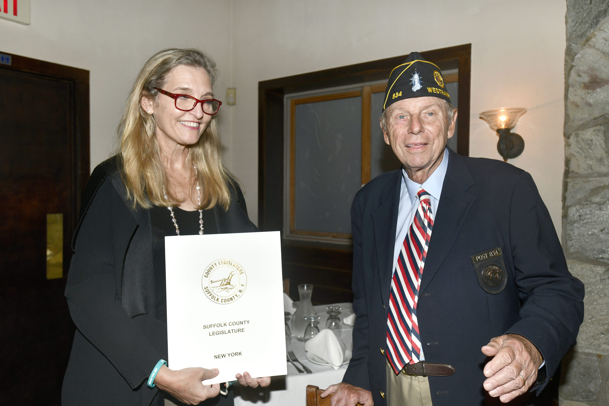Irene Donohue from Suffolk County Legislator Bridget Fleming's office presents a proclamation to Tom Hadlock, Commander of the American Legion Arthur Ellis Hamm Post 834 in Westhampton, in honor of the post's 100th anniversary on Thursday, September 17, at the Baby Moon restaurant. DANA SHAW