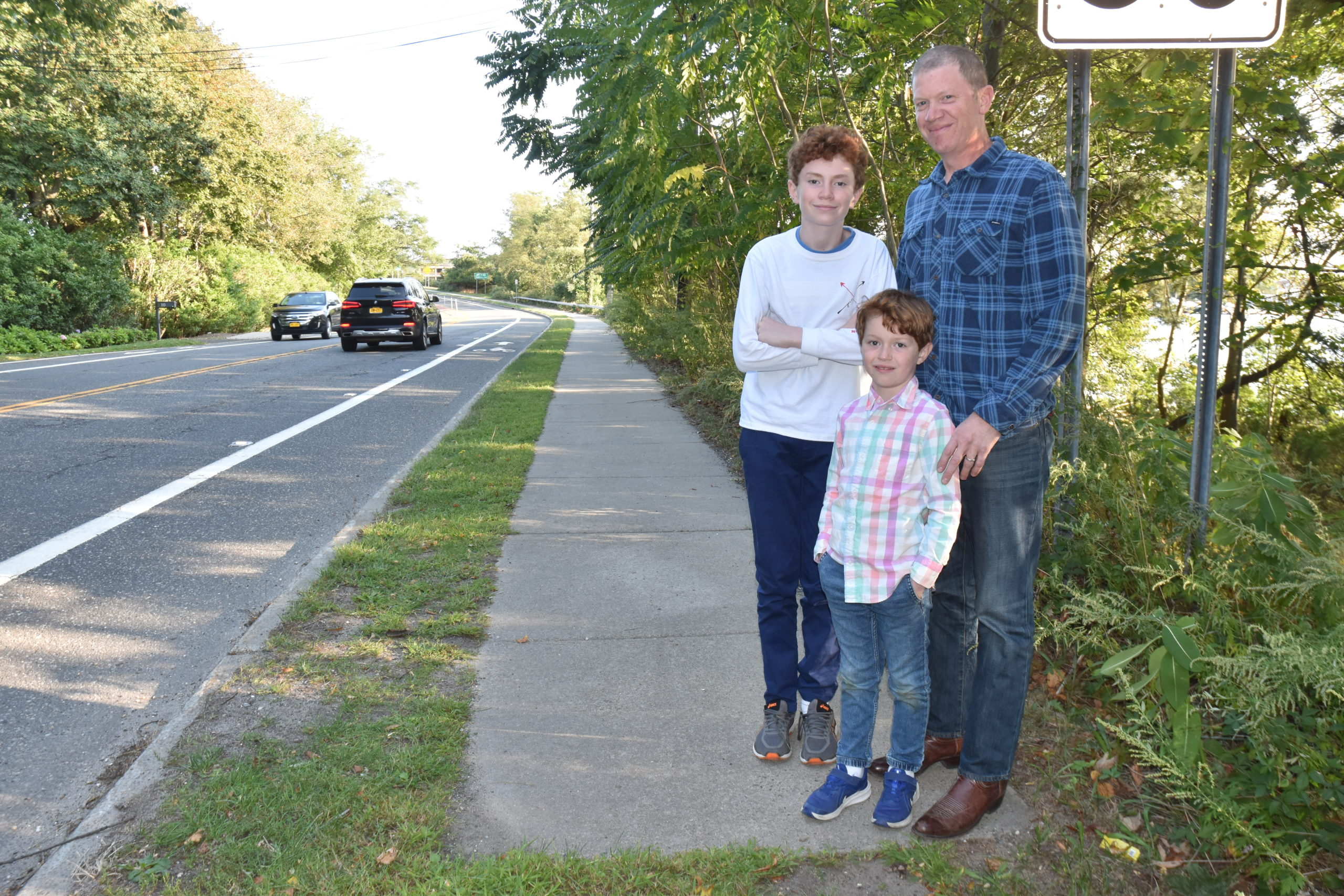North Haven resident Alex Kriegsman, with his sons David, center, left, and Roger, is calling for safer bicycle and pedestrtian lanes along Route 114 in the village. STEPHEN J. KOTZ