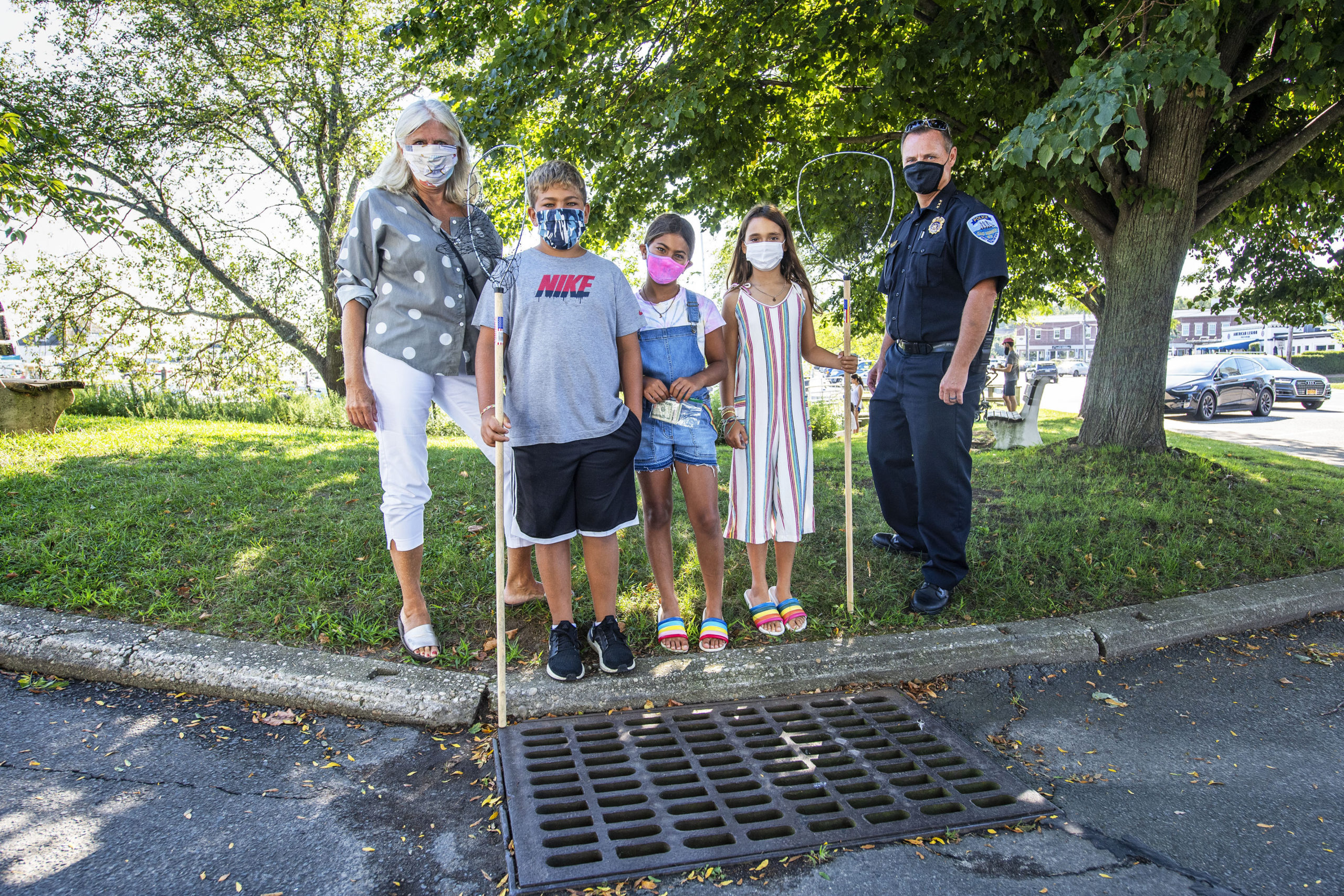 Kyle and Elle Maslin, along with their friend Lila Wiesenthal, pose for a photo with Sag Habor Village Mayor Kathleen Mulcahy and Police Chief Austin McGuire at the storm drain at the corner of Marine Park and Bay Street where the kids, with help from Chief McGuire, rescued a young duckling that was caught in the drain. MICHAEL HELLER