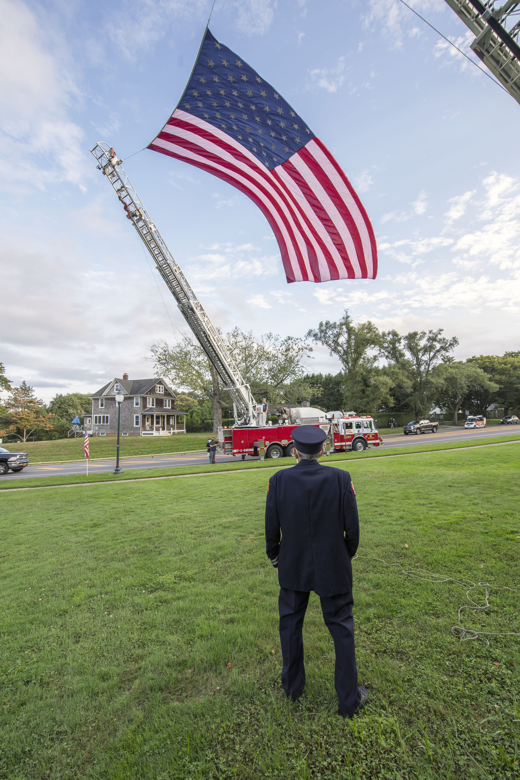 East Hampton Fire Department 50+ year member Joseph DeCristofaro looks up at a large american flag hoisted by EHFD and Sag Harbor FD ladder companies as members of the East End Fire, EMS and Police Departments held a memorial service on the village green in East Hampton commemorating the 19th anniversary of the September 11 attacks.