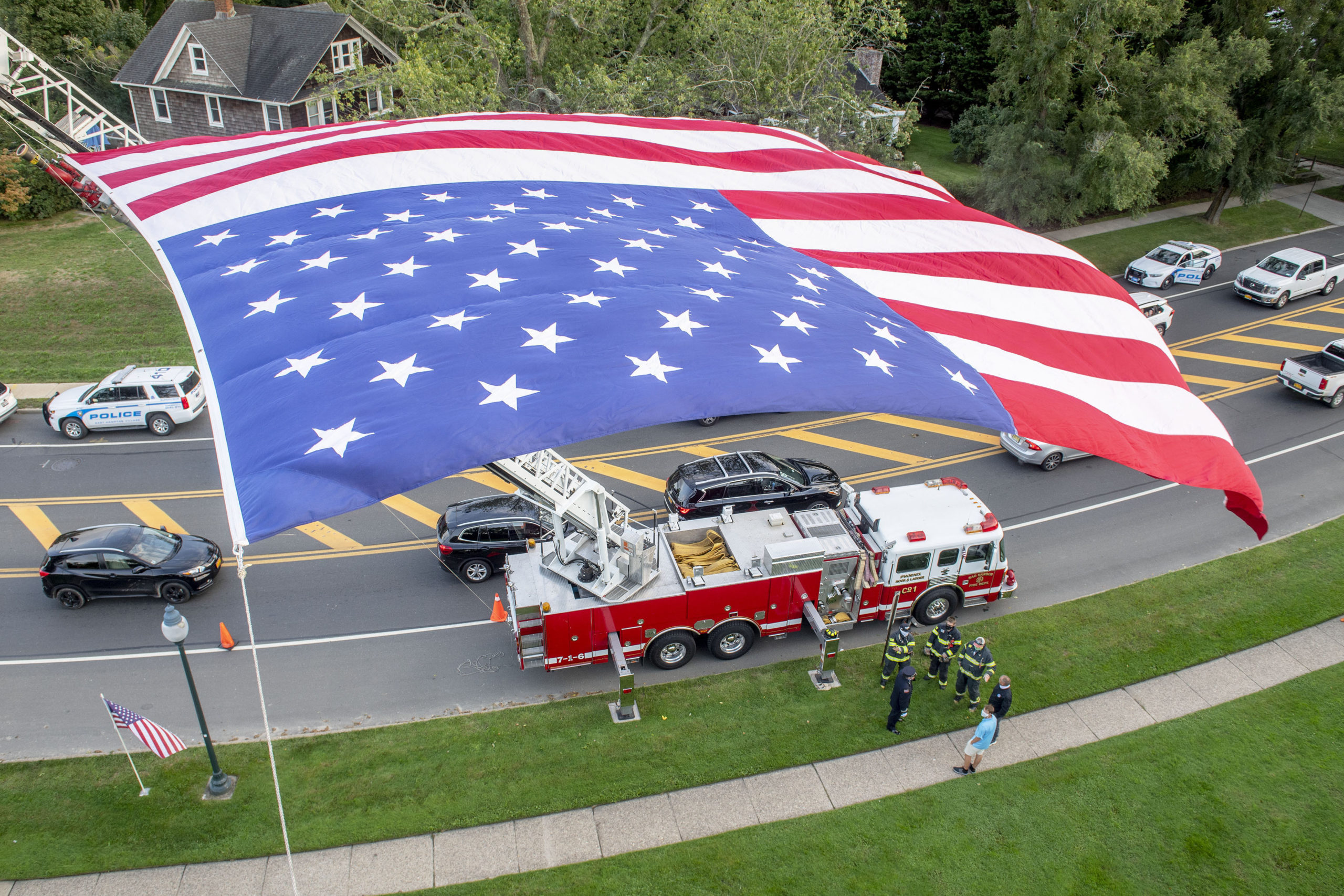 Sag Harbor firefighters gather under a large american flag hoisted by East Hampton and Sag Harbor ladder companies as members of the East End Fire, EMS and Police Departments held a memorial service at the village green in East Hampton commemorating the 19th anniversary of the September 11, 2001 terrorist attacks.