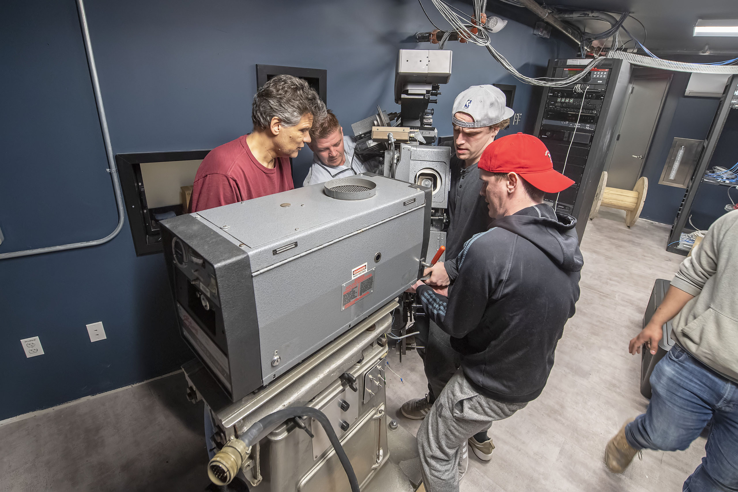 A 200, plus, pound top section of a 35mm projector is muscled into position by a team of four men in its new home in the projection room of the new Sag Harbor Cinema in March.  MICHAEL HELLER