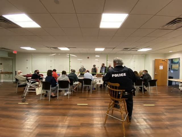 Candidates, their representatives and attorneys set up behind a plexiglass shiled to begin the arduous count of absentee ballots, as a village police officer looks on. DANA SHAW