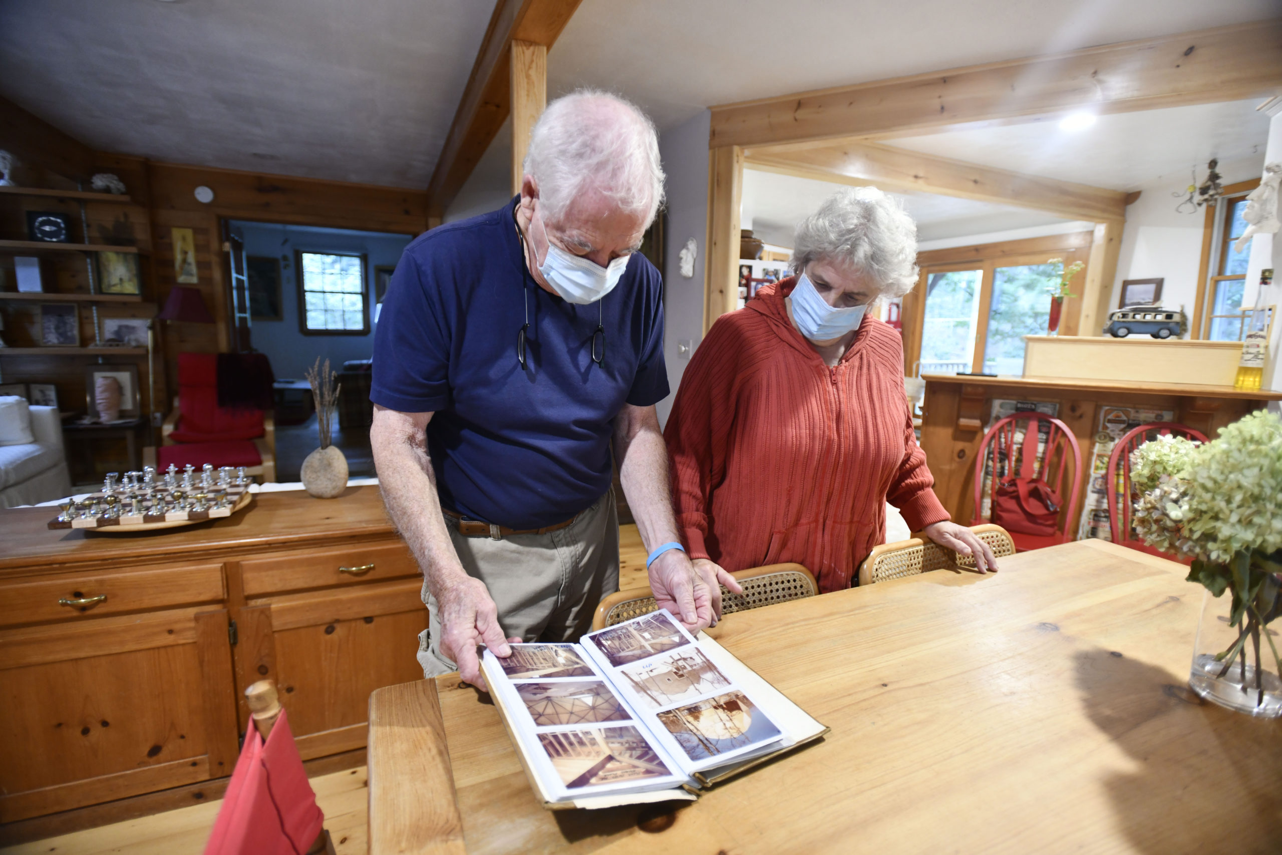 Jim and Jane Baringer look over an album of photos of the house as it was being constructed.   DANA SHAW