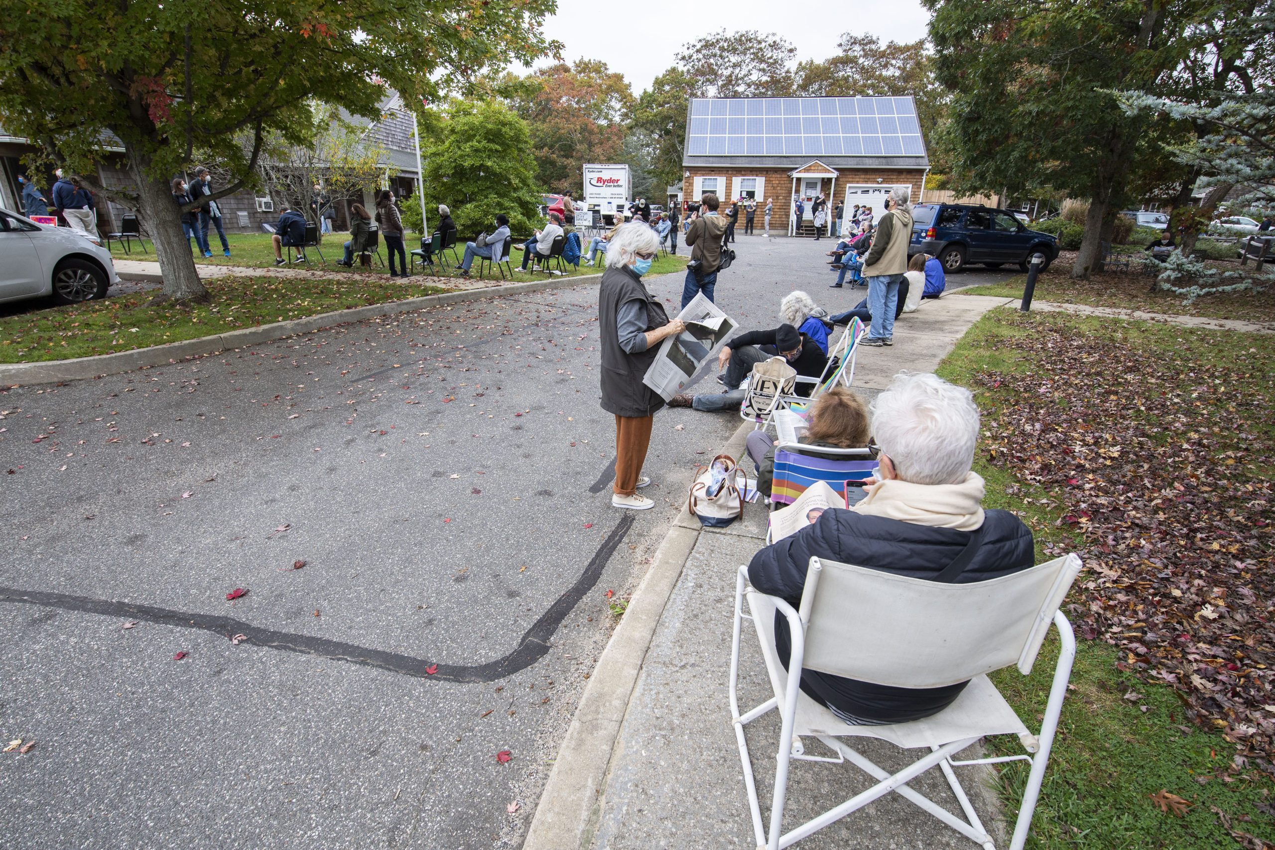 First-arriving voters passed the time by reading and chatting as they waited for the polling center to open during early voting at the Windmill Village complex on Accabonac Road in East Hampton on Saturday morning.  MICHAEL HELLER