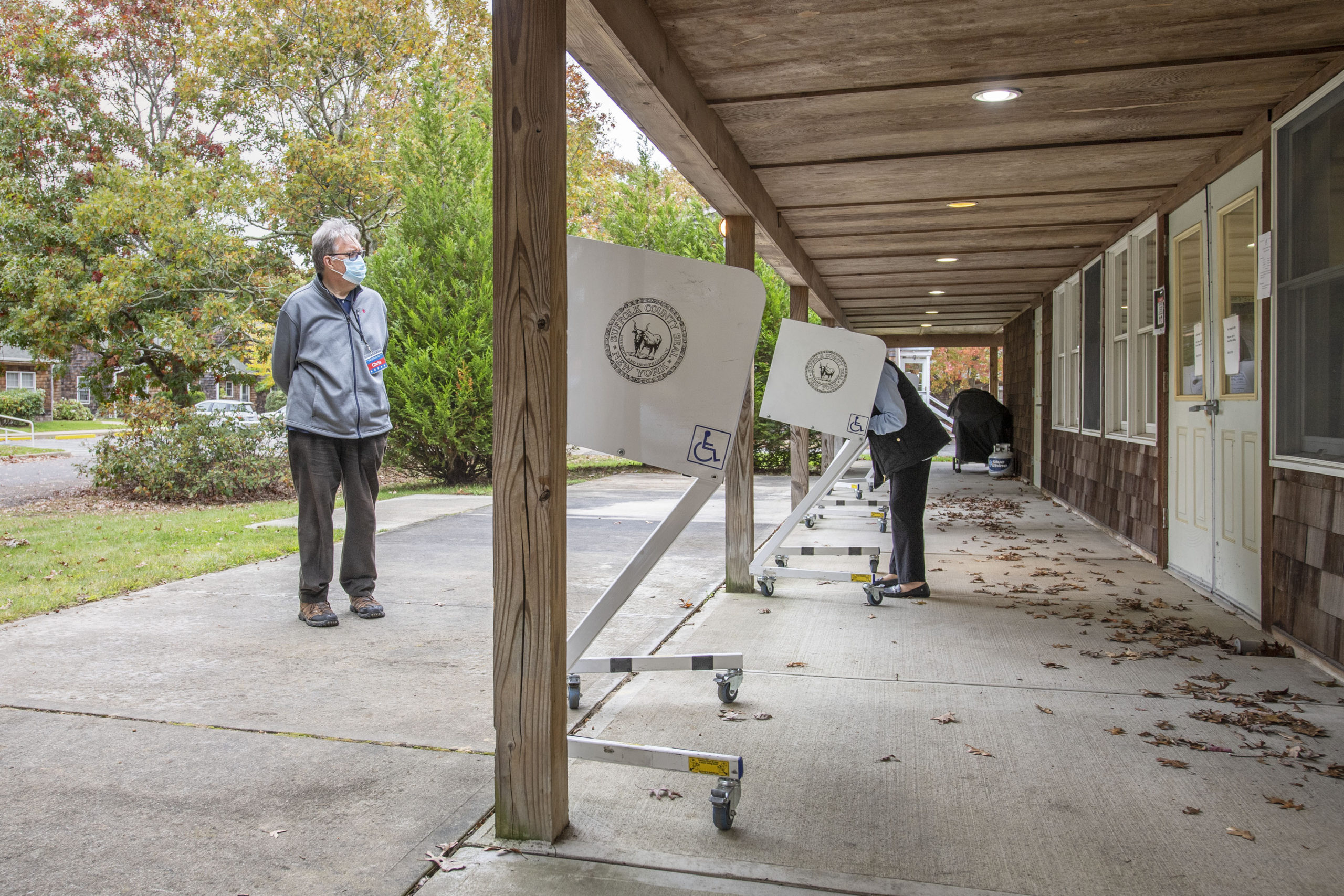 A polling inspector keeps a watchful eye as voters cast their ballots as part of Early Voting in East Hampton Town at the Windmill Village complex on Accabonac Road on Monday morning.   MICHAEL HELLER
