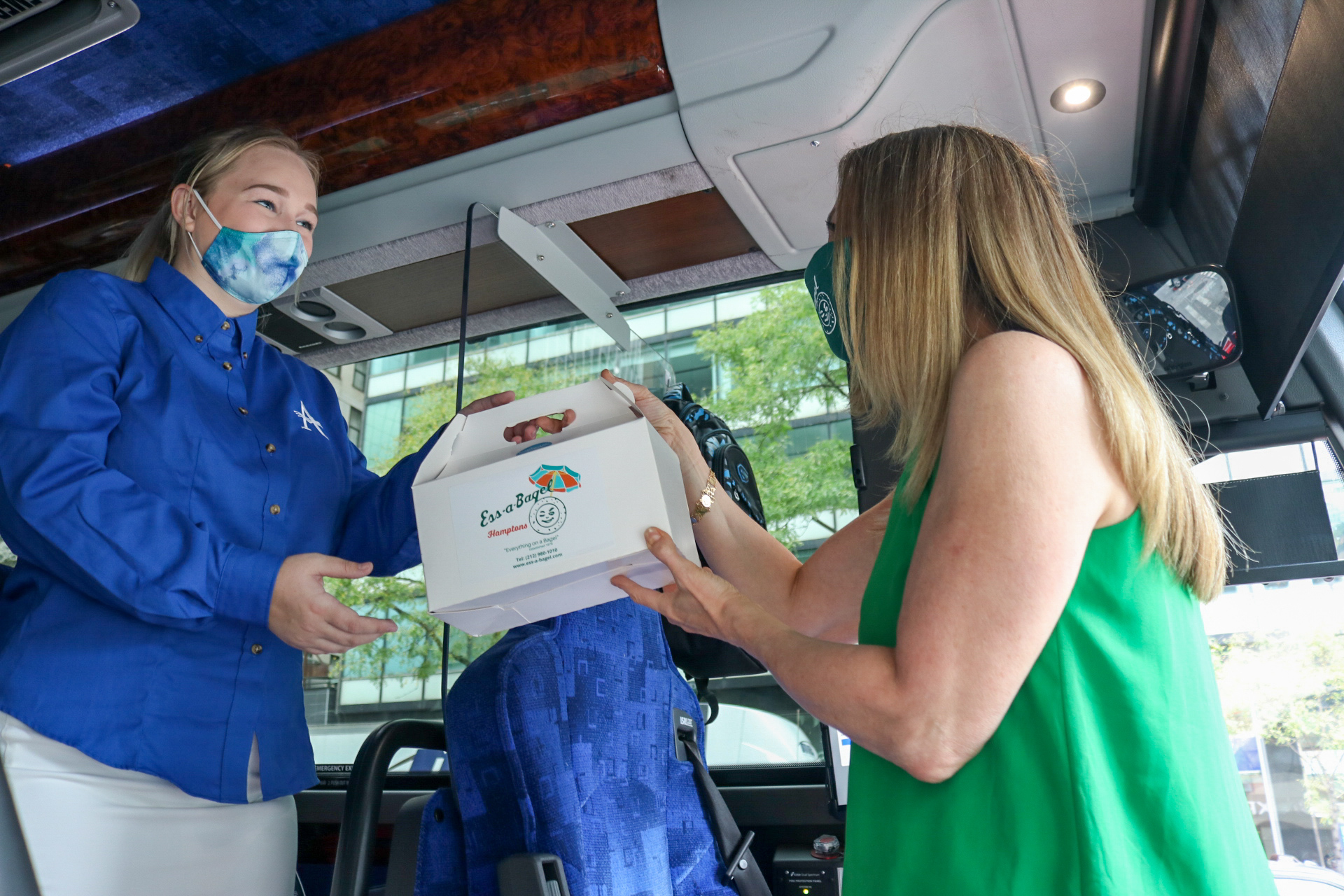 Ess-a-Bagel's COO Melanie Frost hands a bagel package to a member of the Hampton Jitney staff.
