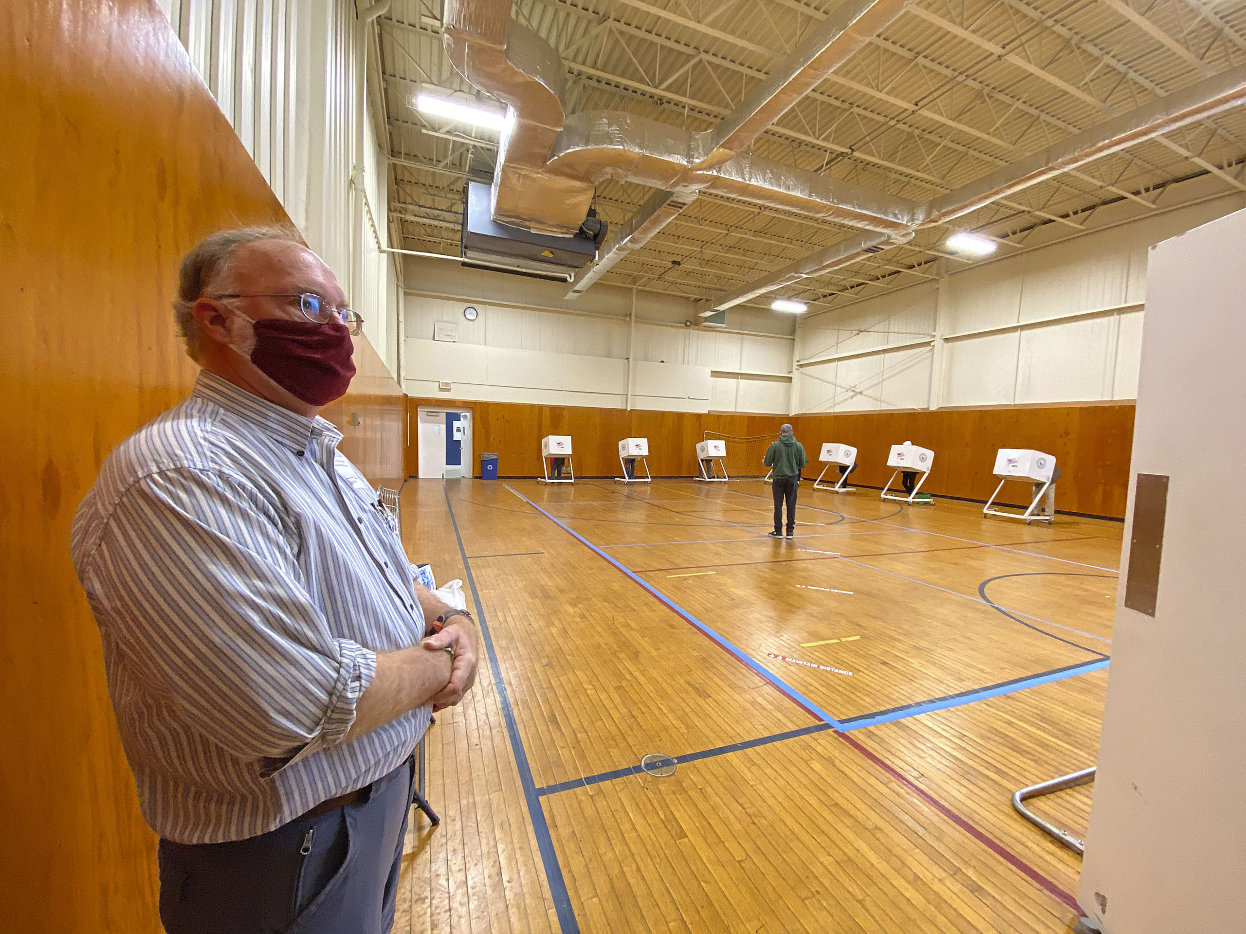 Board of Elections Inspector Charles Guthrie directs voters to booths at the Stony Brook Southampton gym on Monday.  DANA SHAW