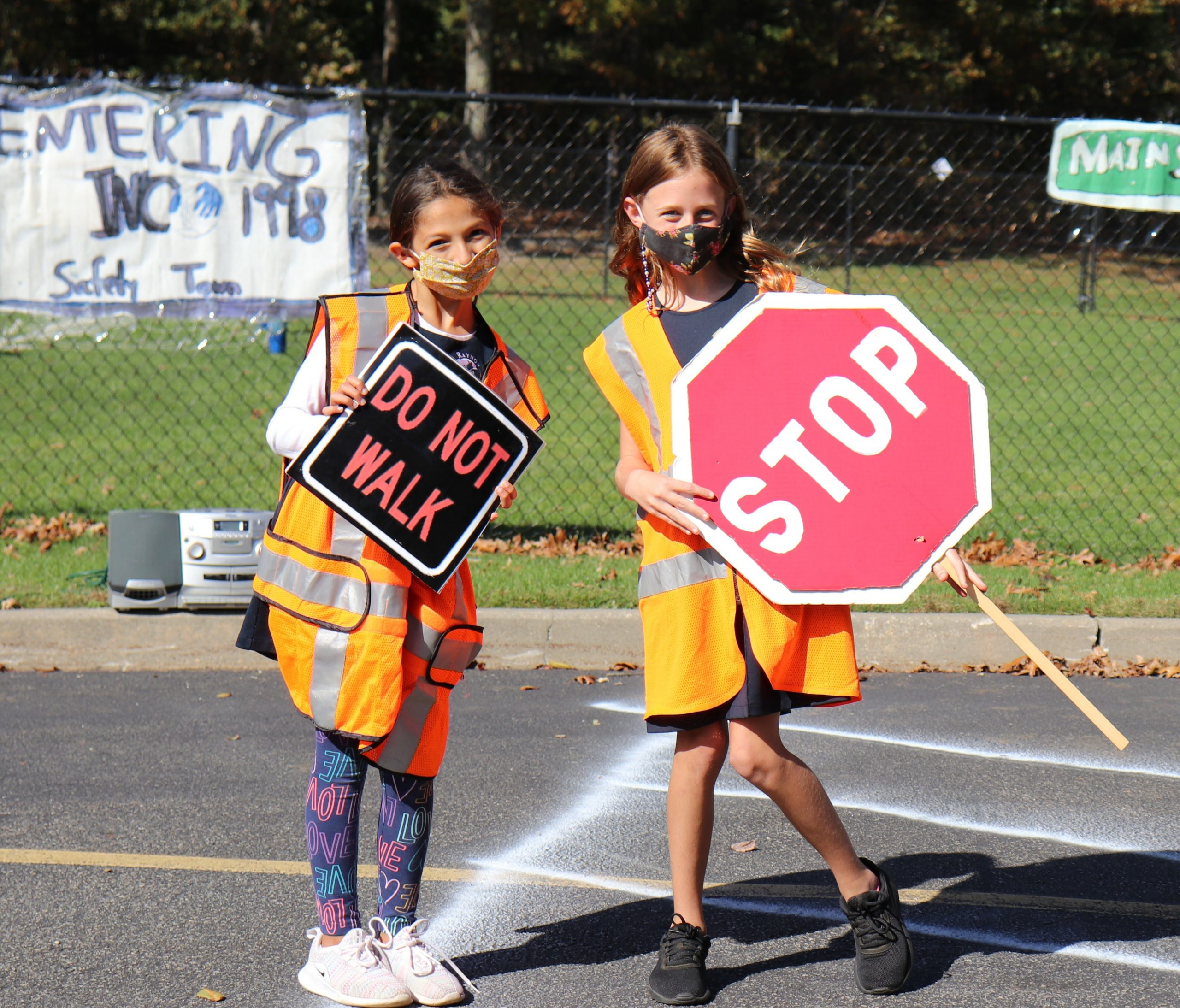 Sixth-grade students, Christina Nikolopoulos and Emery Liere, serve as crossing guards for the annual Tykes on Bikes Safety Town Event.