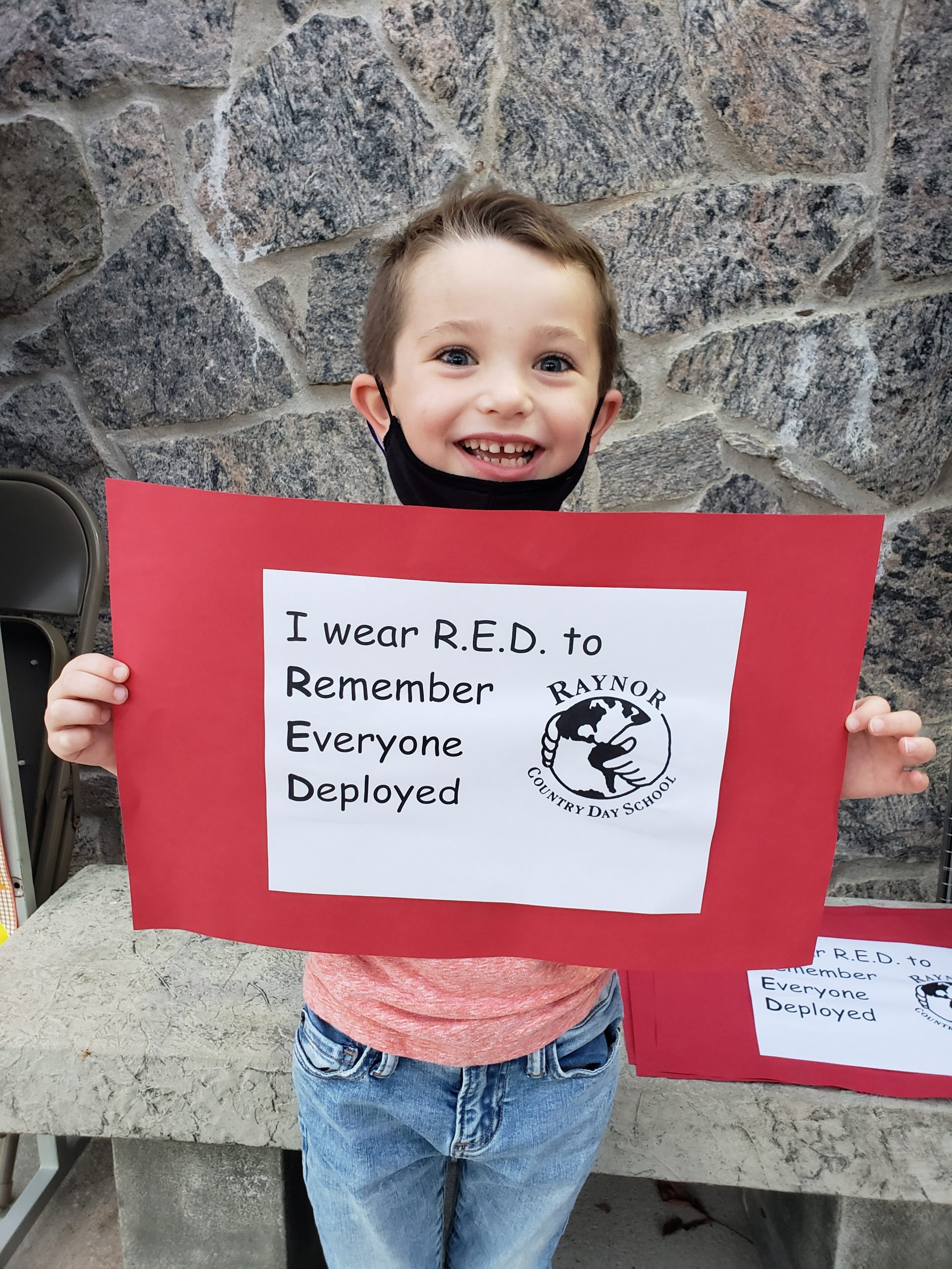 """First-grade student, Christopher Lynch, remembers everyone deployed by participating in Raynor Country Day School's """"Wear Red Friday!"""""""