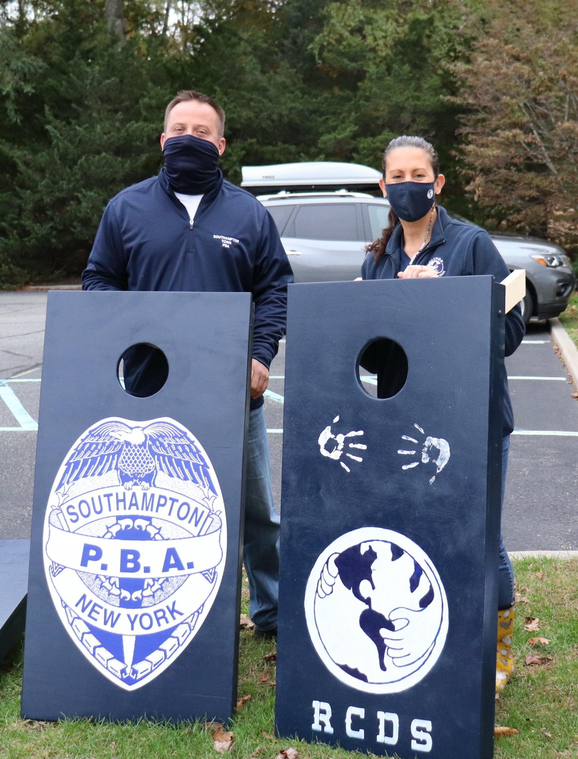 Raynor Country Day School Principal Kerry Coonan and Southampton Town PBA President Erik Bretweiser with the school's new cornhole boards.