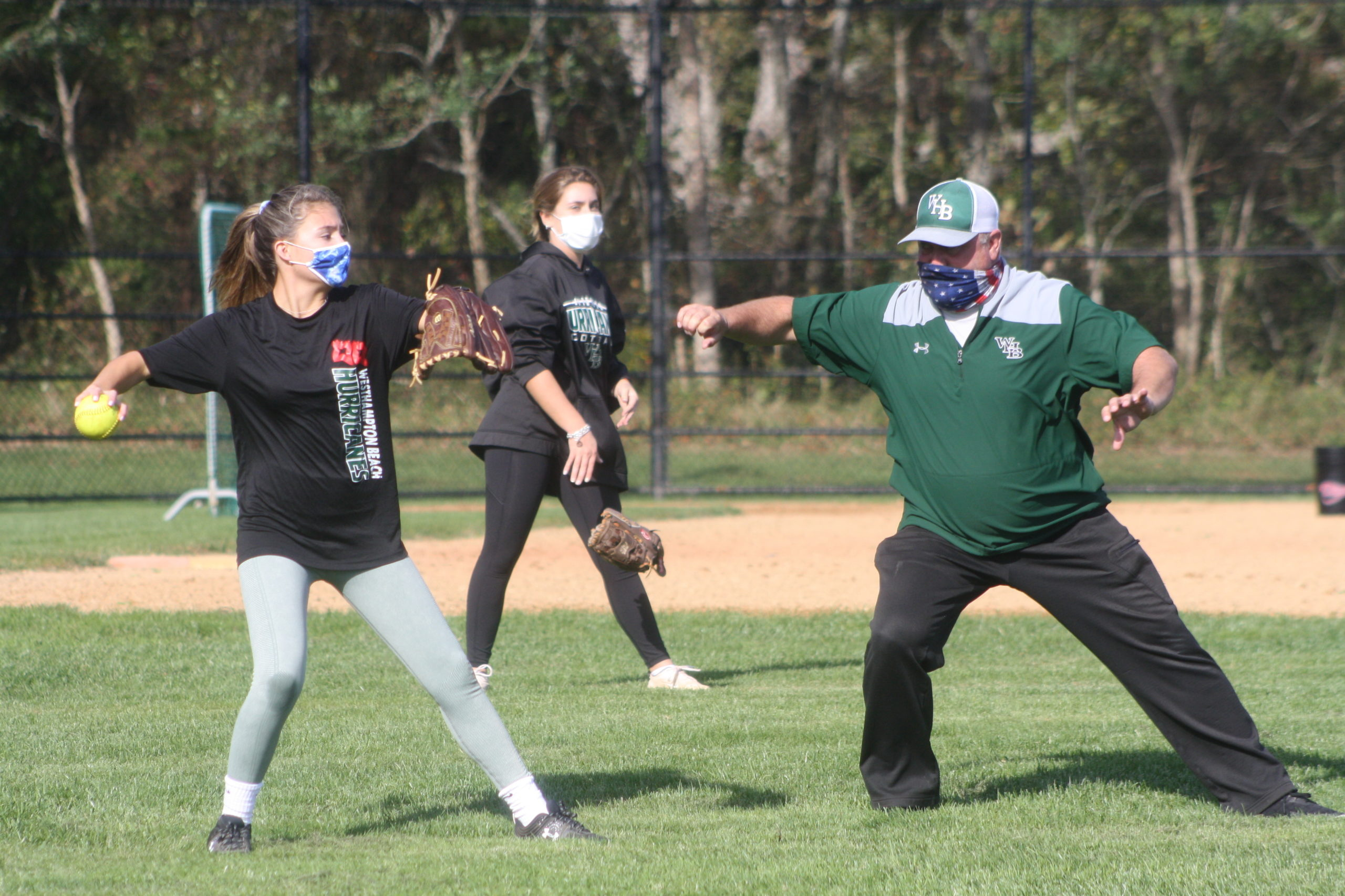Westhampton Beach softball coach Jeff Doroski gives throwing instruction to Marcella Fitzgerald. CAILIN RILEY