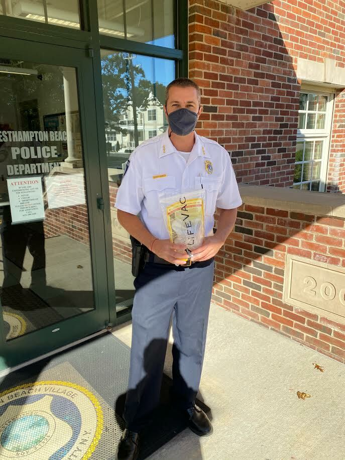 WEsthampton Village Police Chif Trevor Gonce with the LifeVac donated by the Musso family. COURTESY DYAN MUSSO