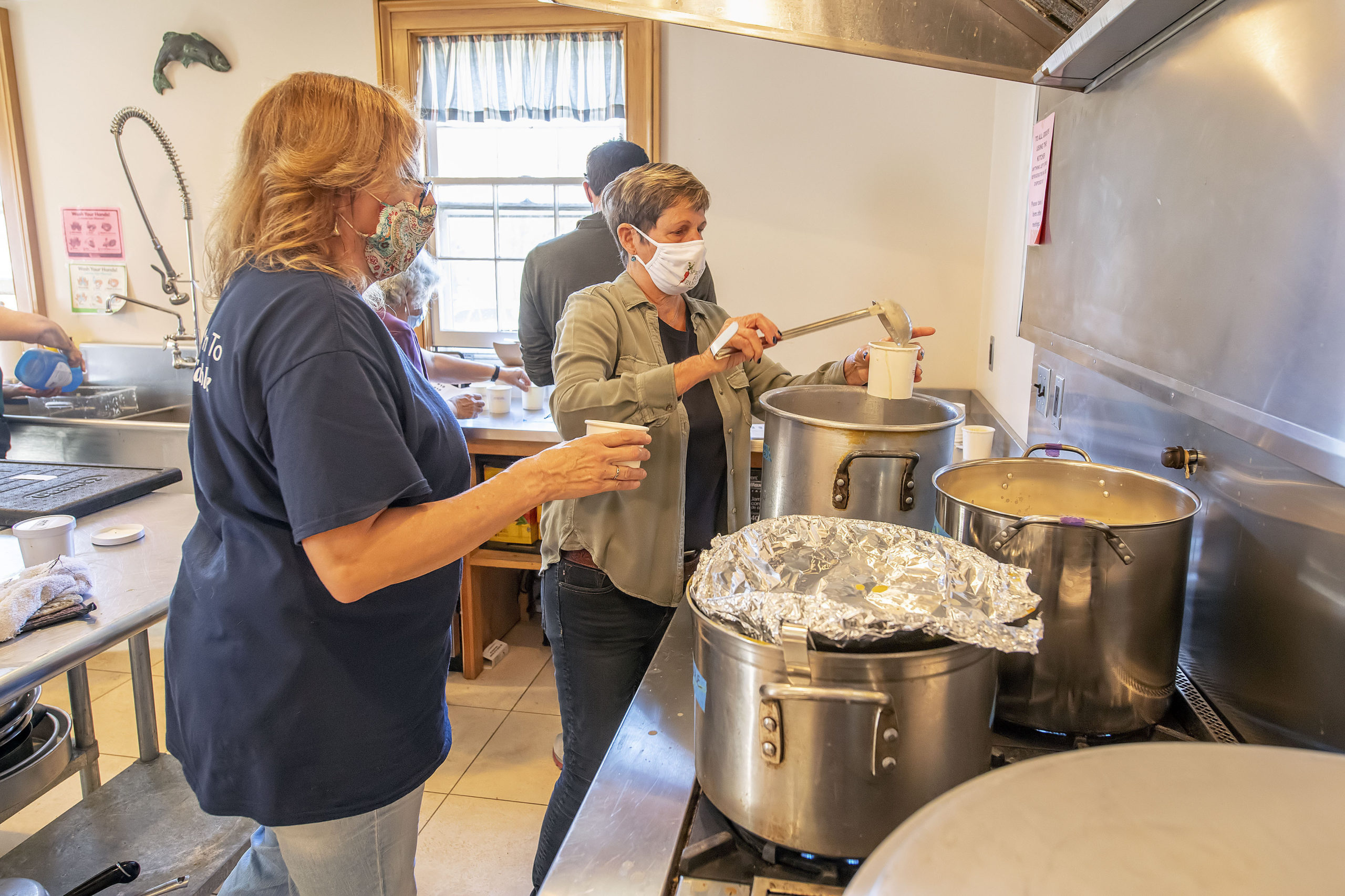 Holly Wheaton ladles out some chowder during the Chowdah Chowdown To Go event at the Springs Community Church on Saturday aftrnoon.  MICHAEL HELLER