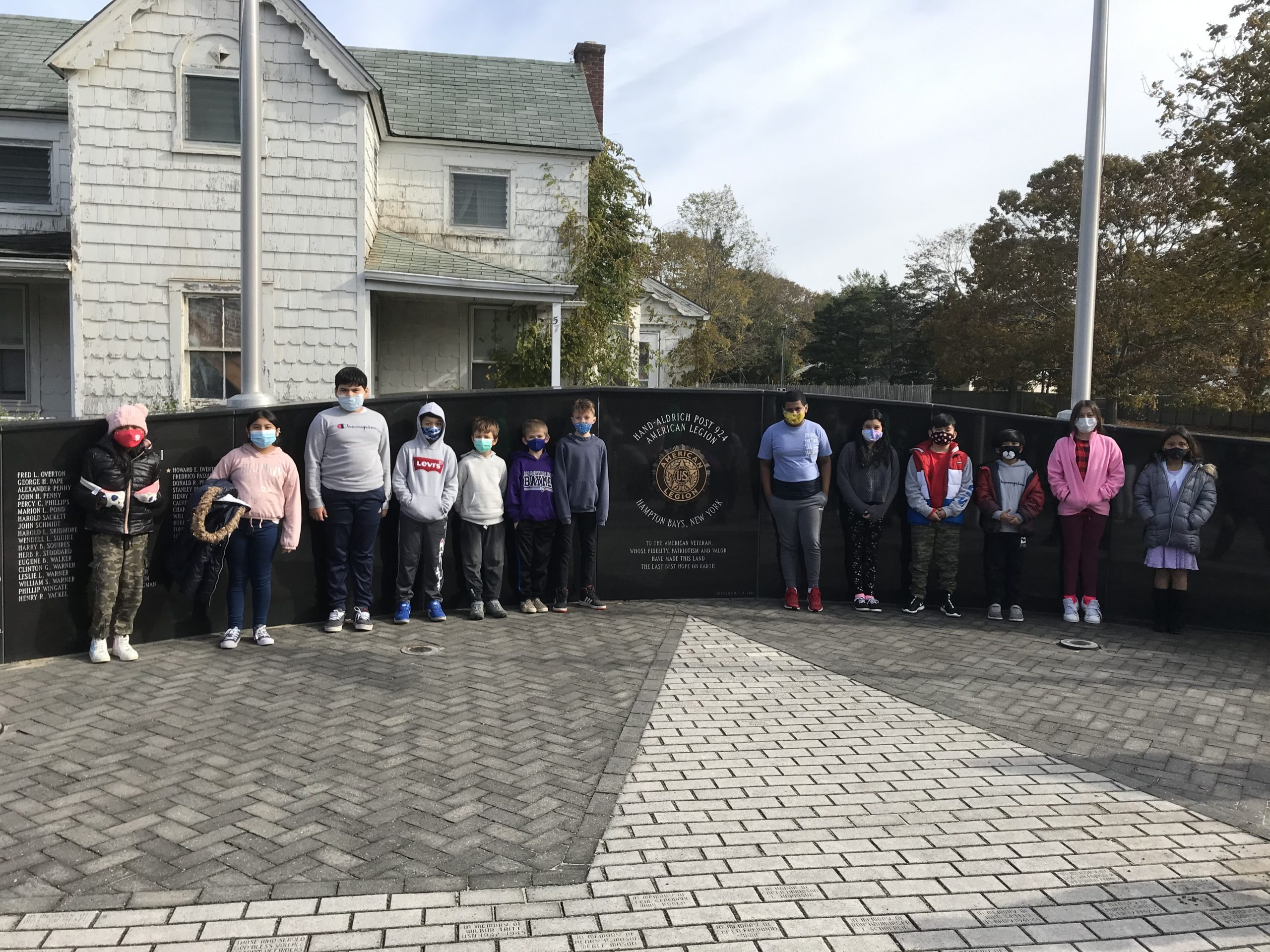As part of a Veterans Day celebration, fourth grade students at Hampton Bays Elementary School took a walking field trip to the community's veterans memorial at the American Legion Post 924 on Ponquogue Avenue. Students learned more about the memorial and spent time speaking with local veterans.
