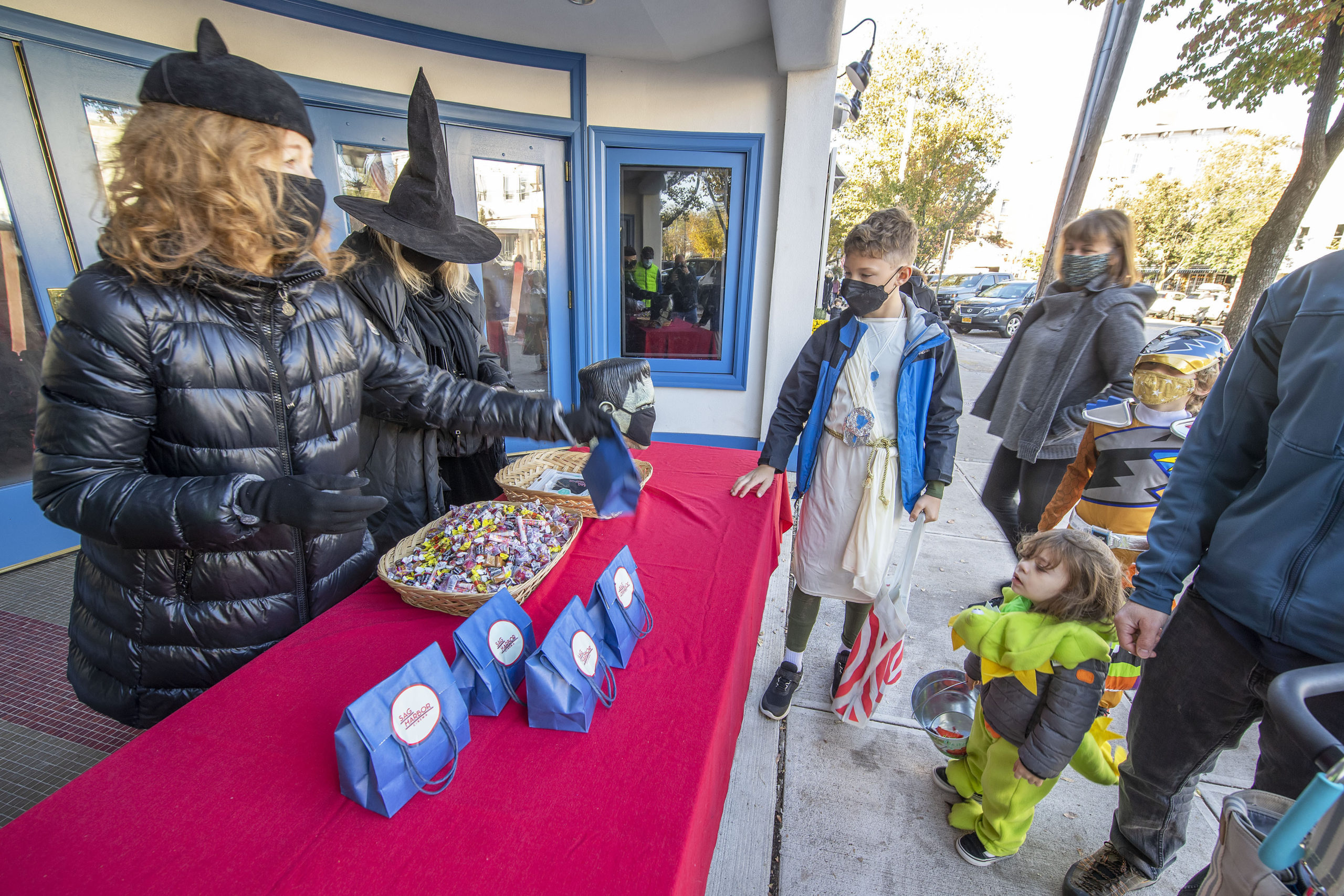 Costumed little ones stopped by the Sag Harbor Cinema to get some candy from April Gornik and Gail Bruesewitz on Halloween afternoon.    MICHAEL HELLER