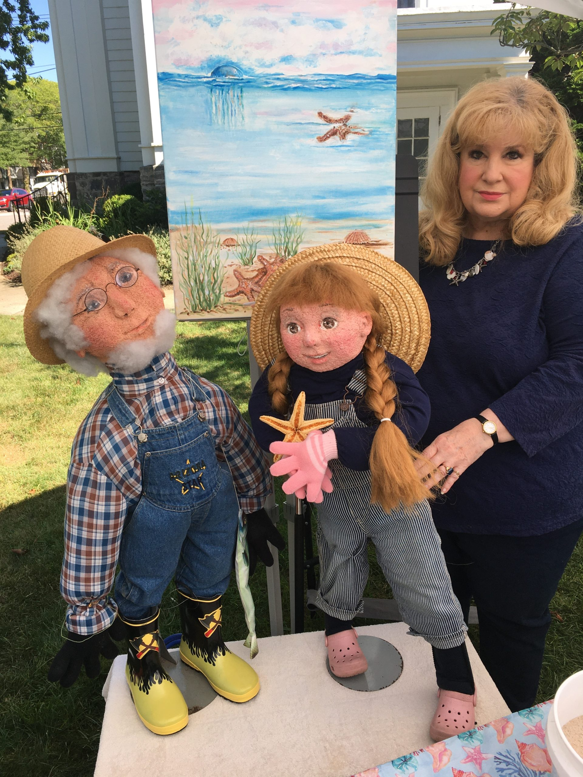Katherine Mades with a painting and the characters from her children's story,