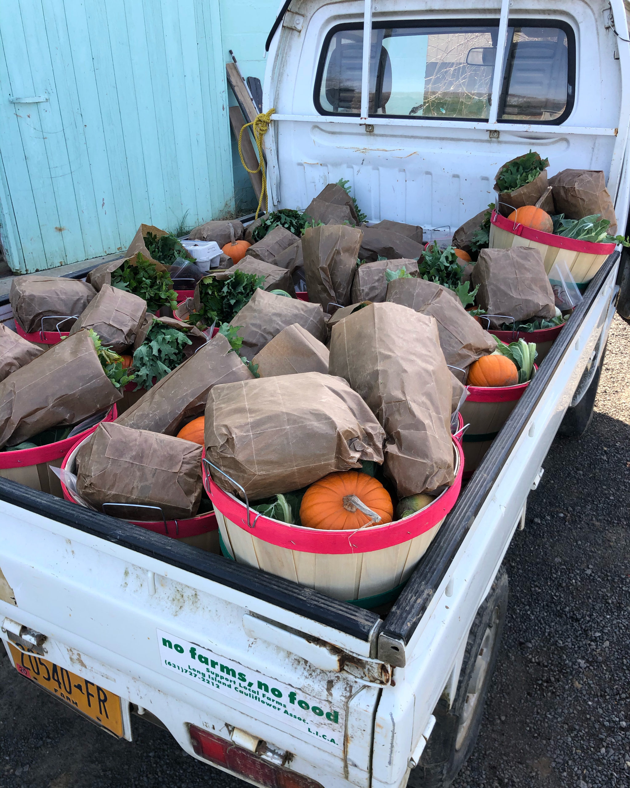 A pick-up truck loaded with bushels filled with Marilee Farmstand CSA shares.