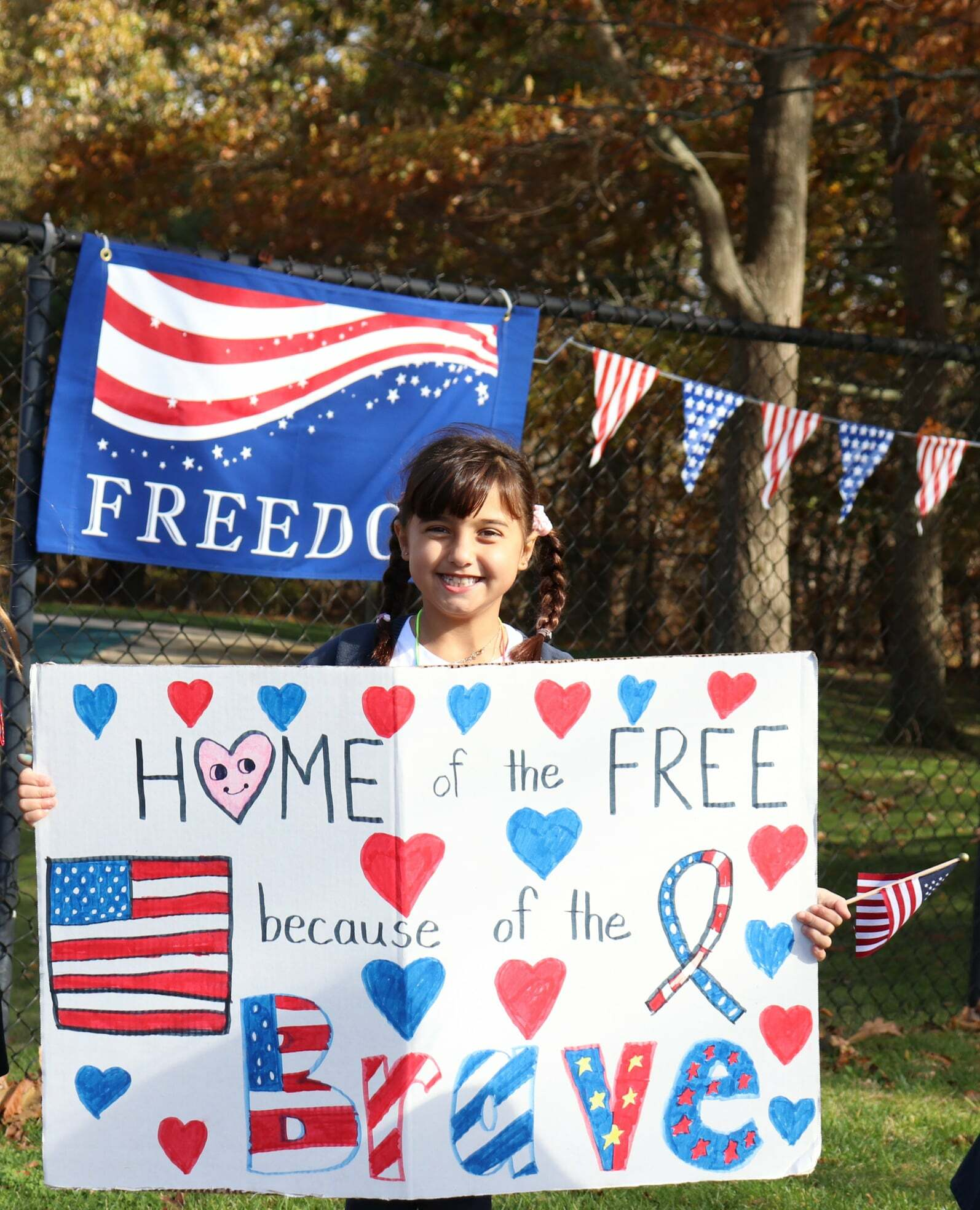Second-grade student, Gigi Trimarco, celebrates the veterans during Raynor Country Day School's annual Celebration.