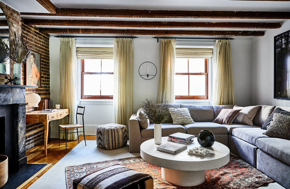 A Bohemian family room in a historic home with exposed brick walls and wooden beamed ceilings.
