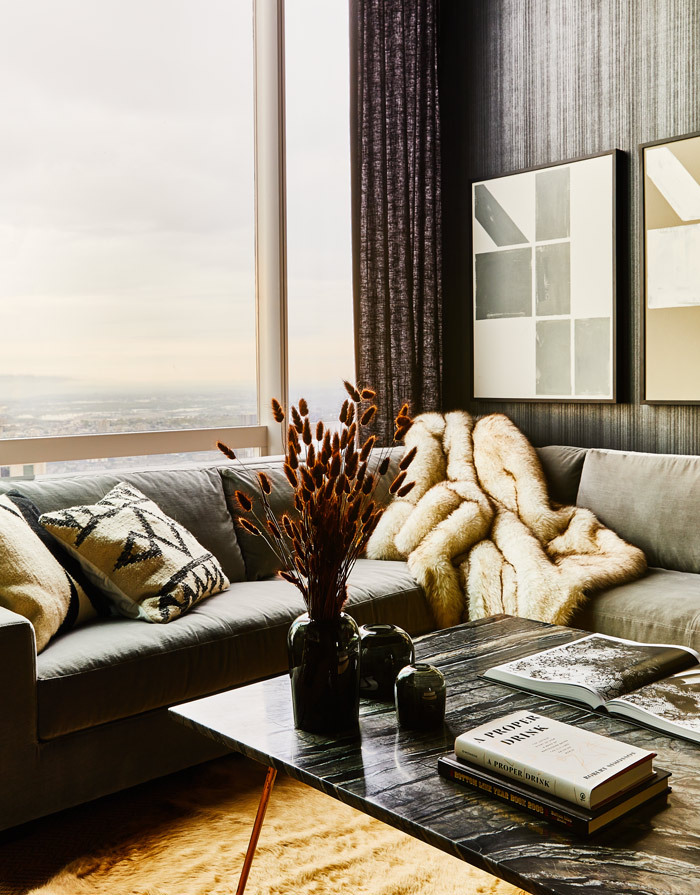 A contemporary family room with floor-to-ceiling windows and black walls.