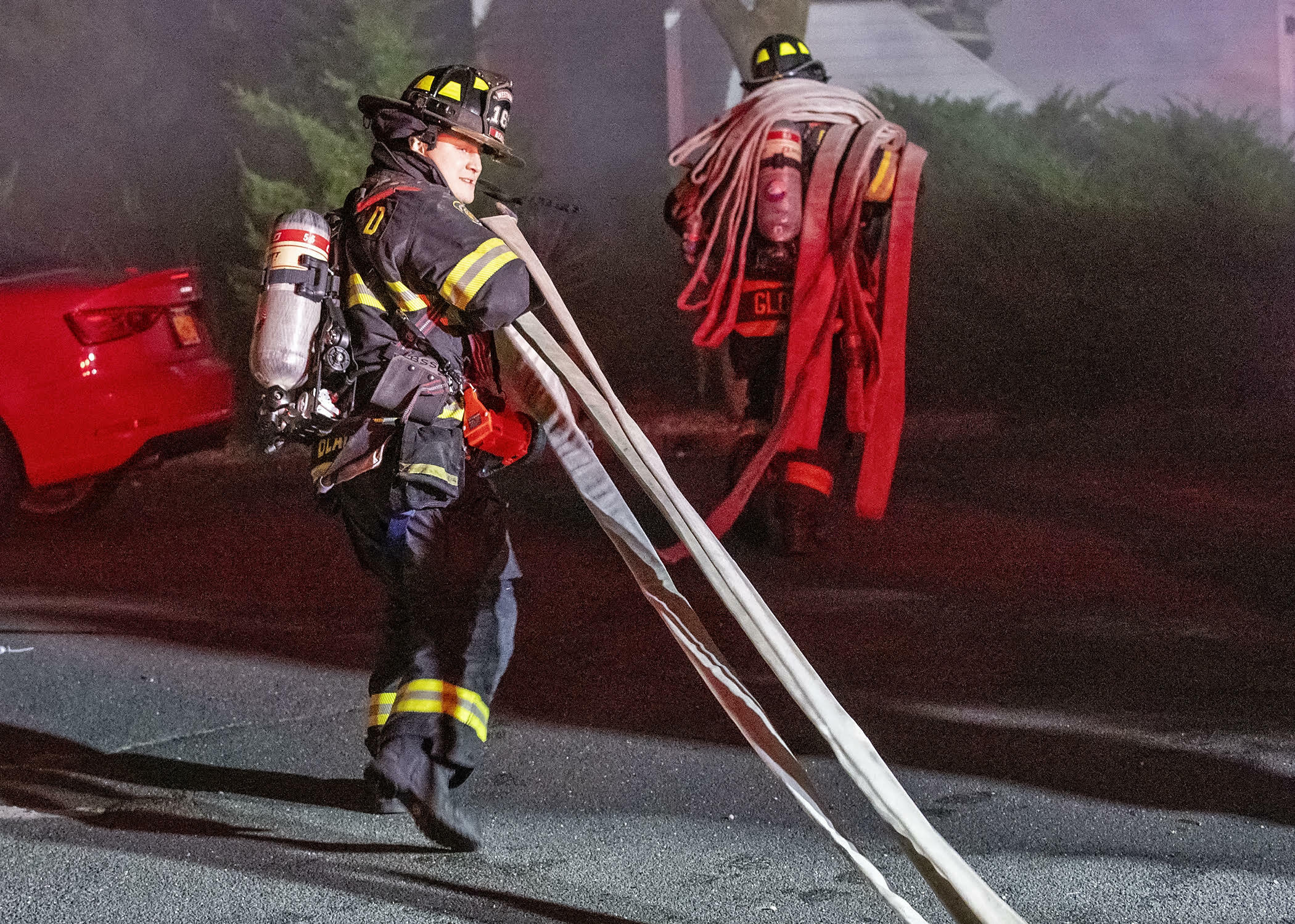 Firefighter reilly bean 9left) and ex-captain tom Glover laying hose. COURTESY WESTHAMPTON BEACH FIRE DEPARTMENT