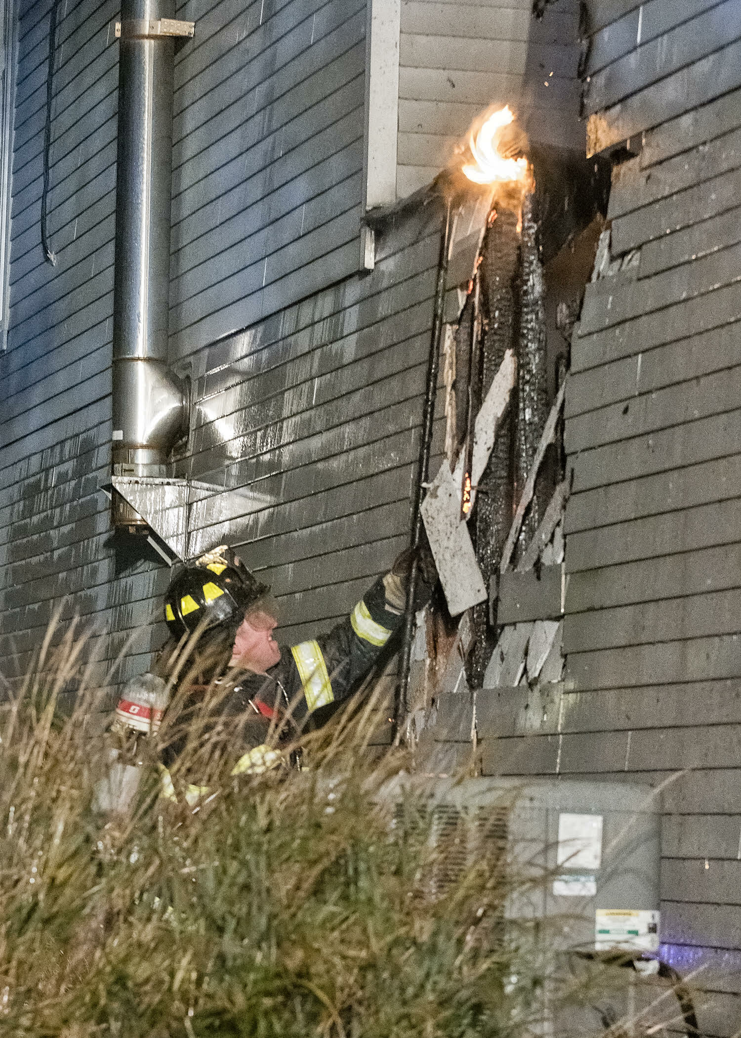 Tom Glover opens up a wall to attack the blaze. COURTESY WESTHAMPTON BEACH FIRE DEPARTMENT