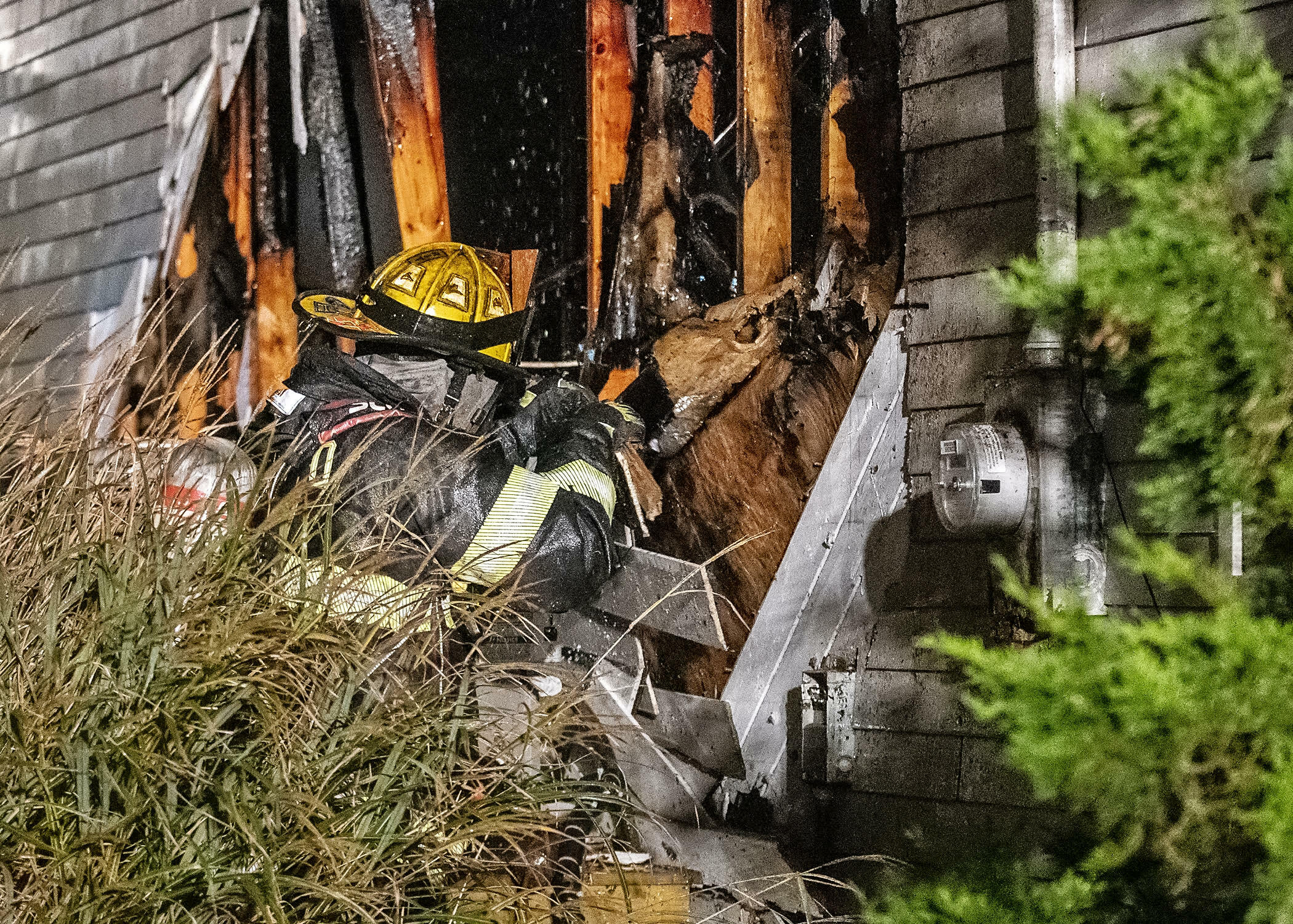 Lt. Robert Eckles, Jr. tears open a portion of exterior wall to expose residenual pockets of fire. COURTESY WESTHAMPTON BEACH FIRE DEPARTMENT