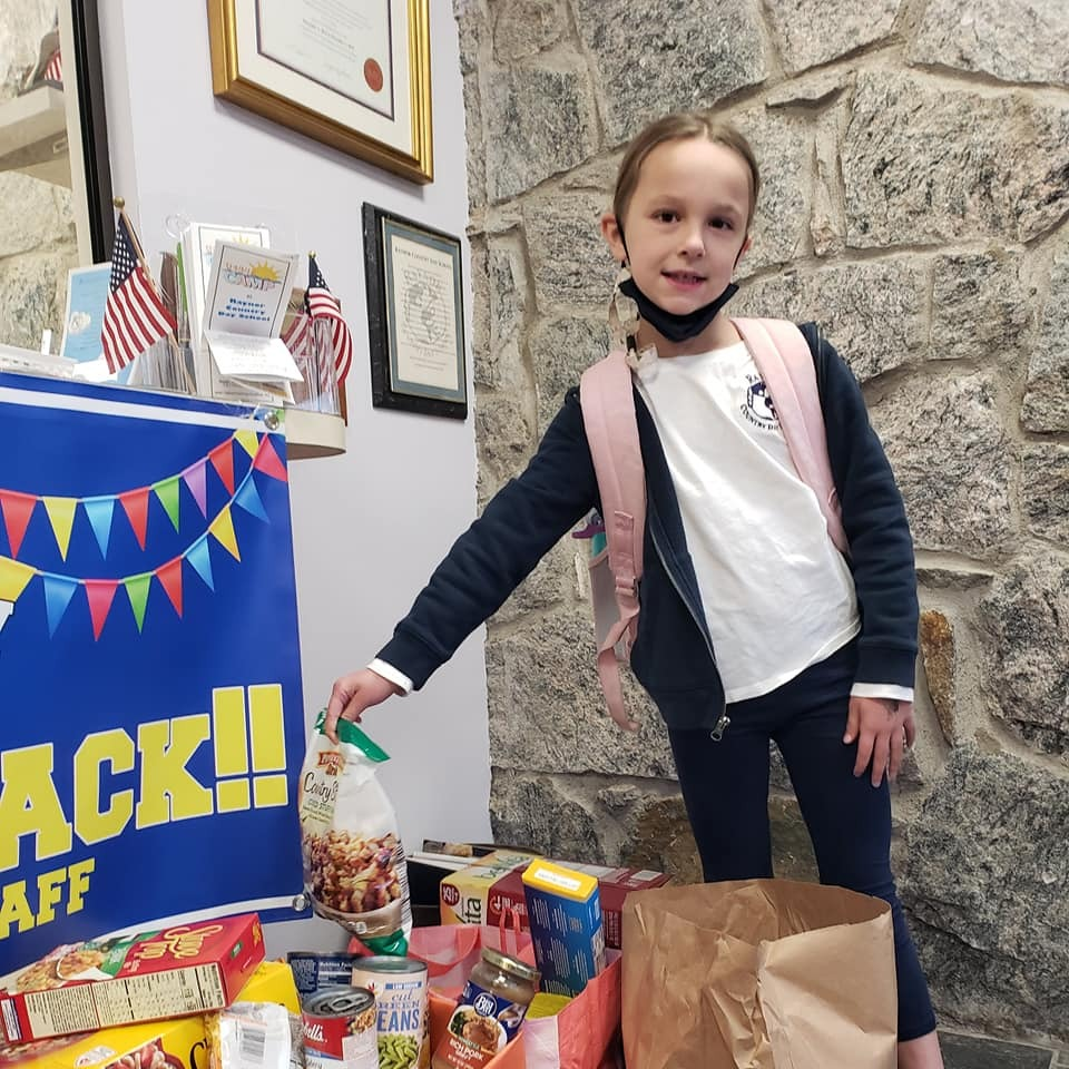 Raynor Country Day School second-grade student, Ariana Raymond, donates food on behalf of the food drive organized by the Southampton Town Police Department. Raynor Country Day School worked in conjunction with local officer, Eric Plum, and collected more than 12 full boxes of canned goods and other food pantry essentials.