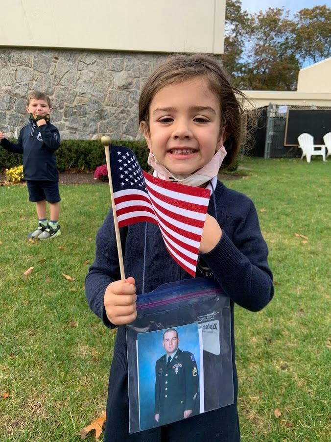 Pre-kindergarten student, Lily Crisci, celebrates the service of her uncle during Raynor Country Day SChool's annual Veterans' Day Celebration.