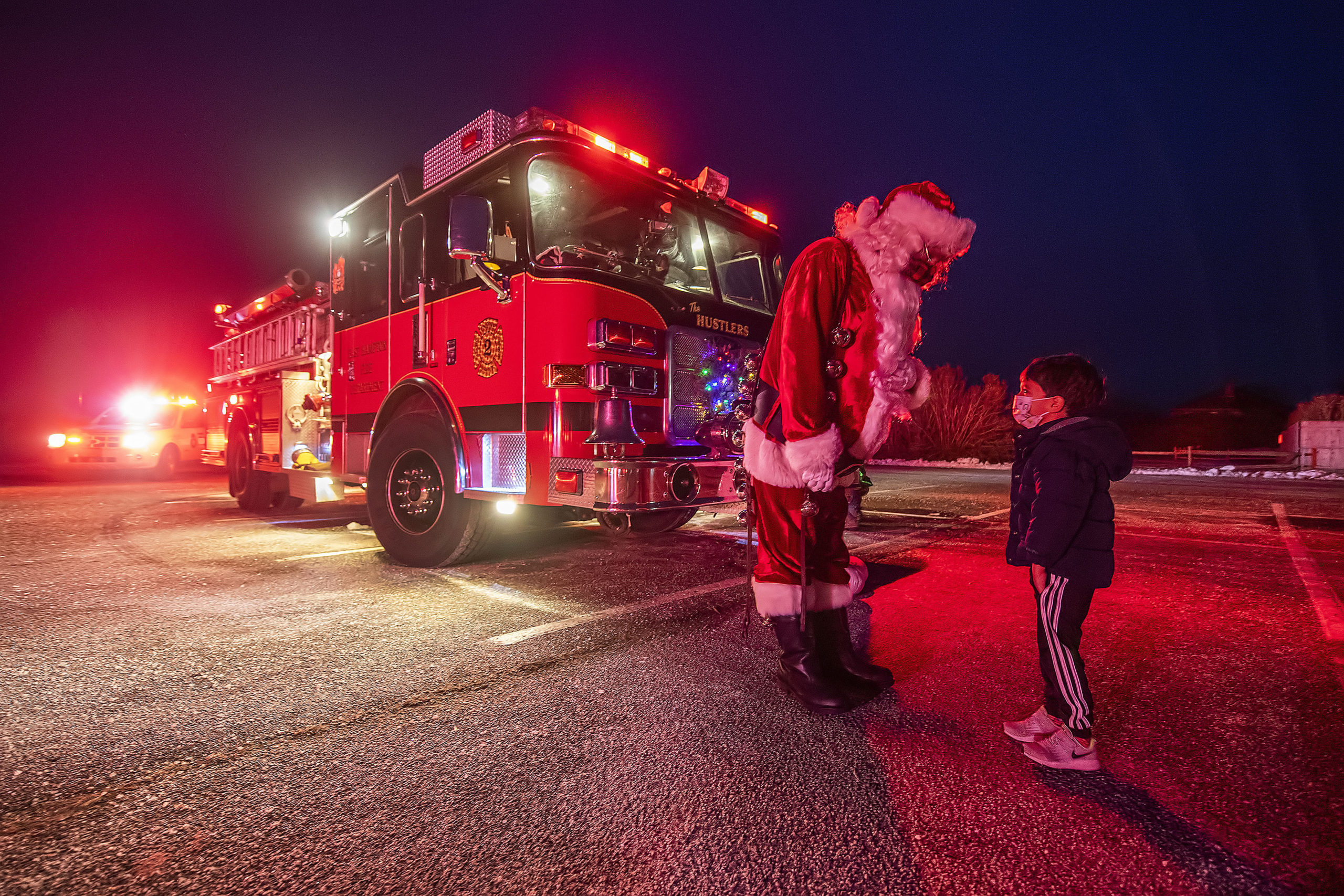 Three-year-old Wyatt Utsch has a private conference with Santa - who arrived courtesy of East Hampton Fire Department Engine Company #2 - during the Movies on Main Beach - East Hampton Drive-In screening of