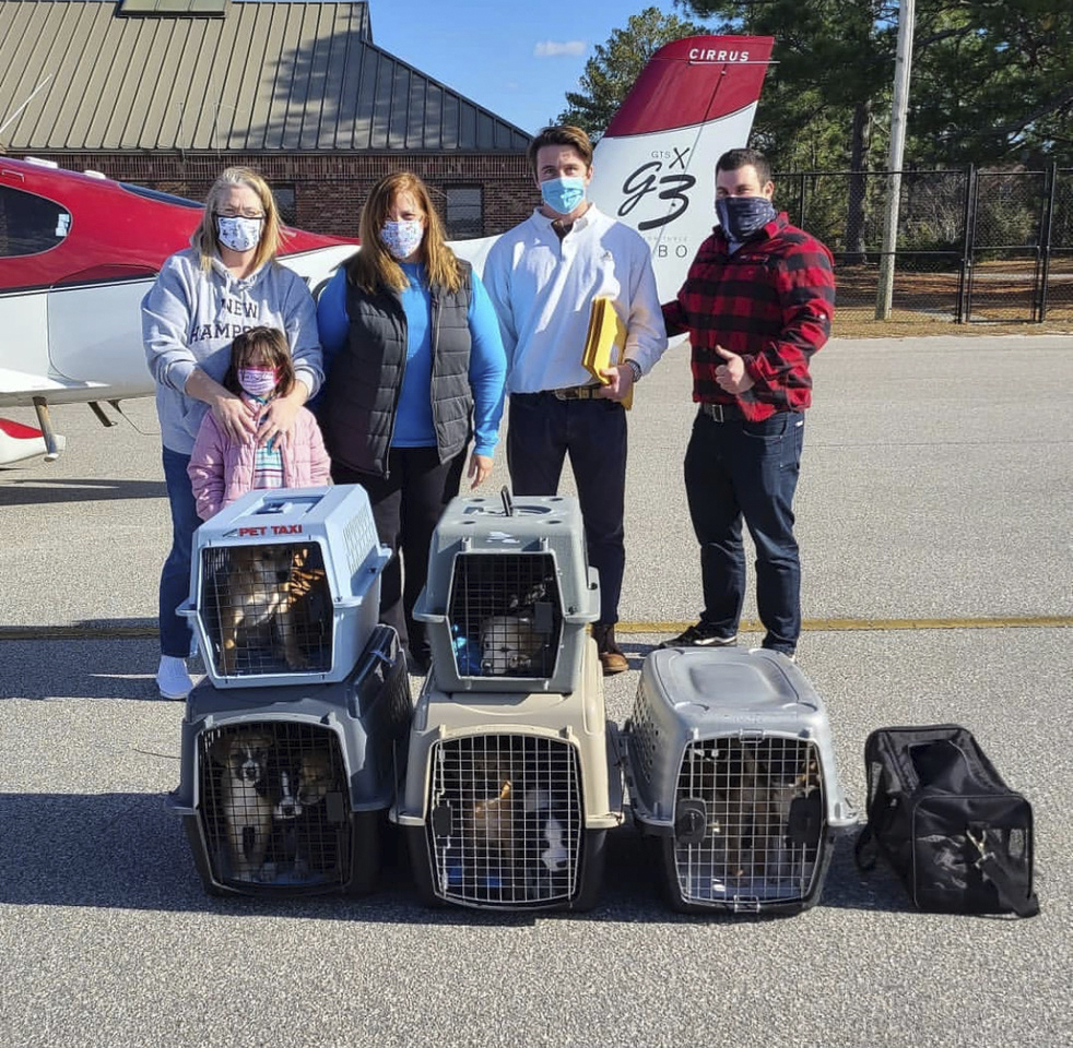Volunteers from Fostering Foster Animal Rescue at the airport in Camden, South Carolina, with pilots Charles Canavan and Brian LaBelle (right), the owner of the airplane that carried 15 puppies to East Hampton Airport fort delivery to ARF. COURTESY CHARLES CANAVAN