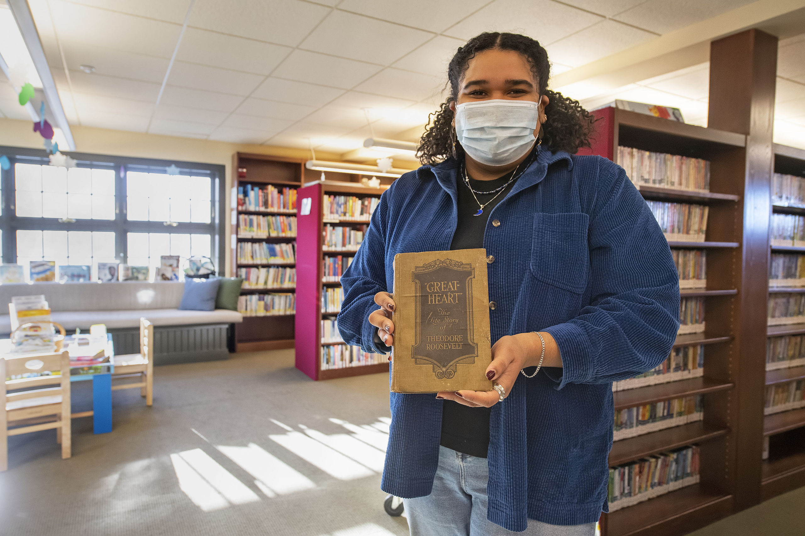 Librarian Julianna Vargas accepted the overdue book from John Moss, who found it in a crate of old books he had ins storage. MICHAEL HELLER PHOTOS