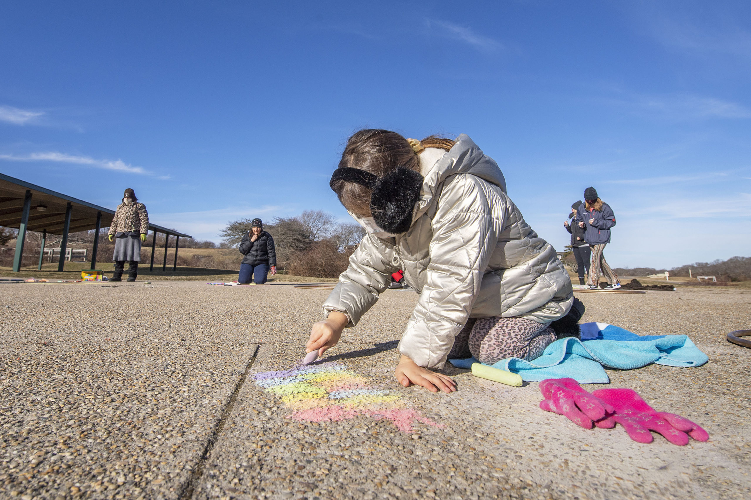 Six-year-old Grace Grimshaw works on her masterpiece during a chalk-drawing get-together hosted by Kate Mueth and the Neo-Political Cowgirls at the Third House grounds in Montauk on Sunday.     MICHAEL HELLER