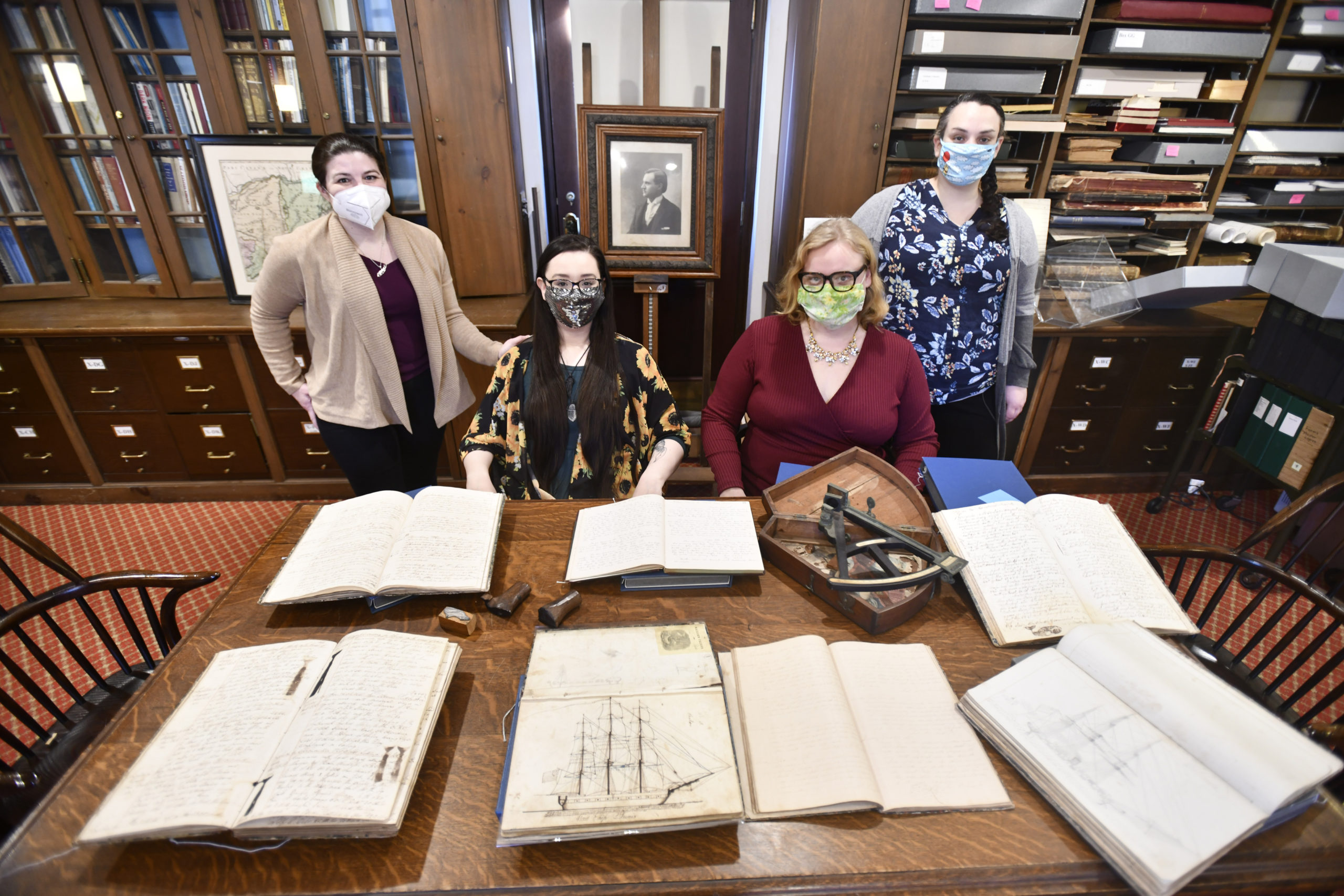In the Long Island Collection at the East Hampton Library with some of the whaling logs they digitized are, standing, left to right, Andrea Meyer and Mayra Scanlon. Seated, seated, Tina Ambrosecchia and Julia Tyson.   DANA SHAW
