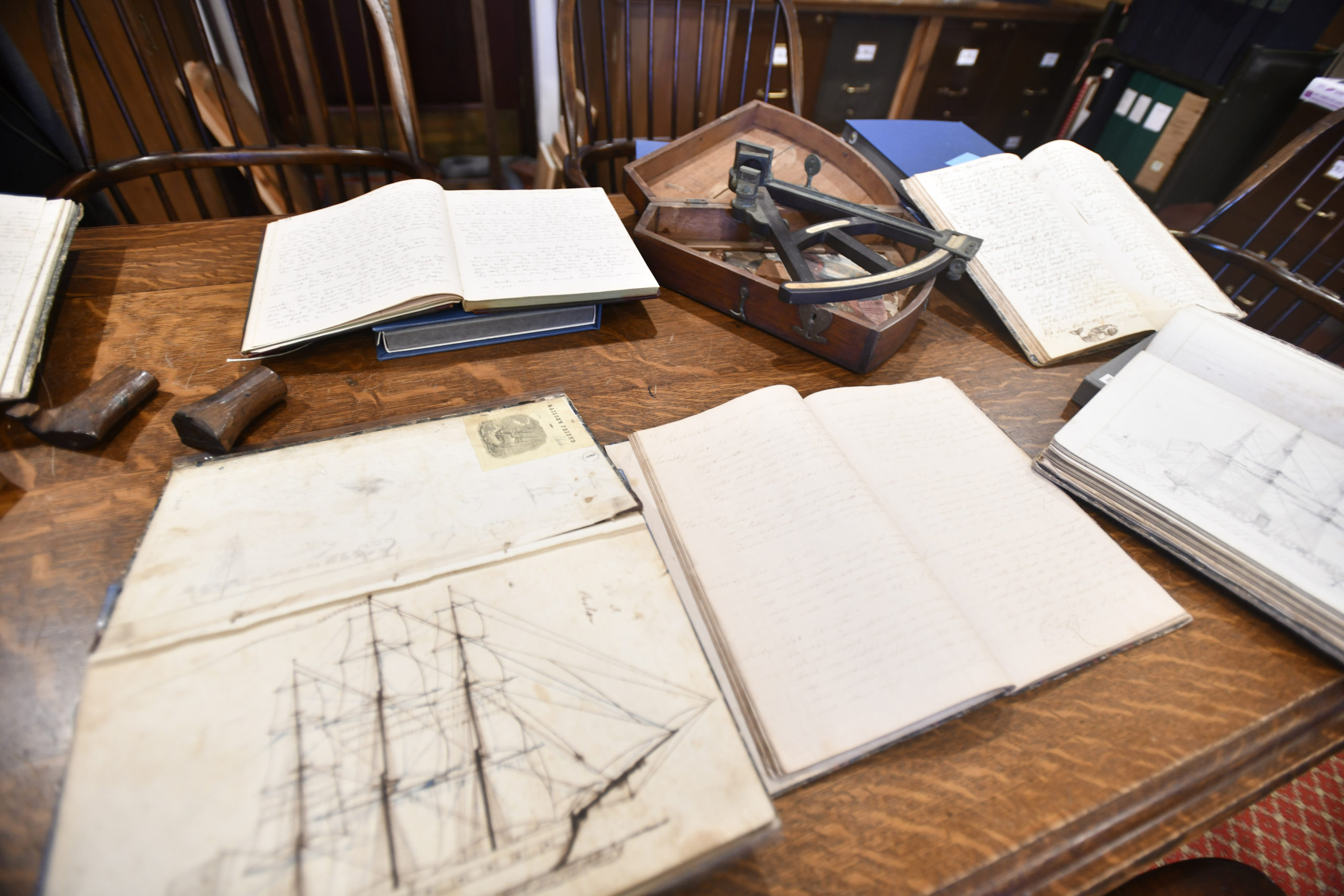 Some of the whaling logs and items from the East Hampton Library's Long Island Collection, including a sextant and carved whale stamps.  DANA SHAW
