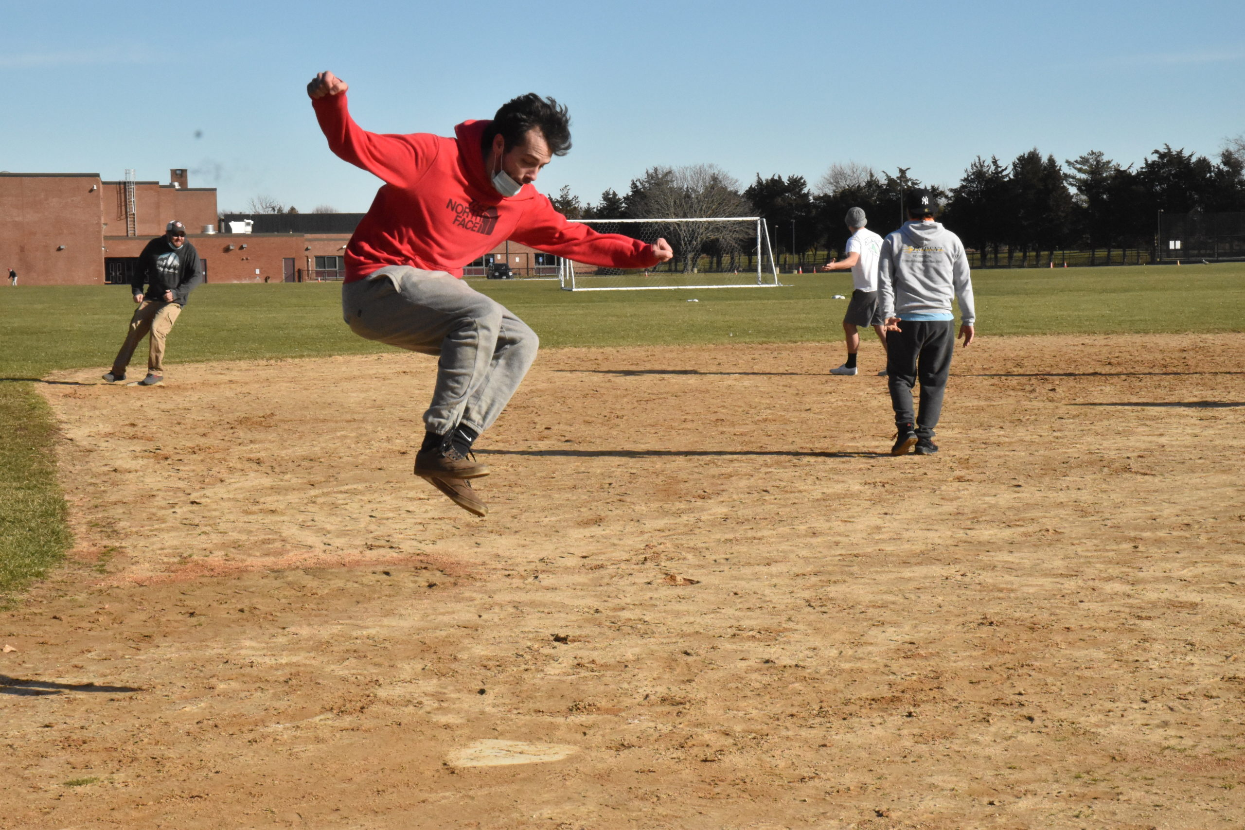Steve Swiderski scores a run with an exclamation point in a pickup kickball game at Southampton Intermediate School on Sunday. STEPHEN J. KOTZ
