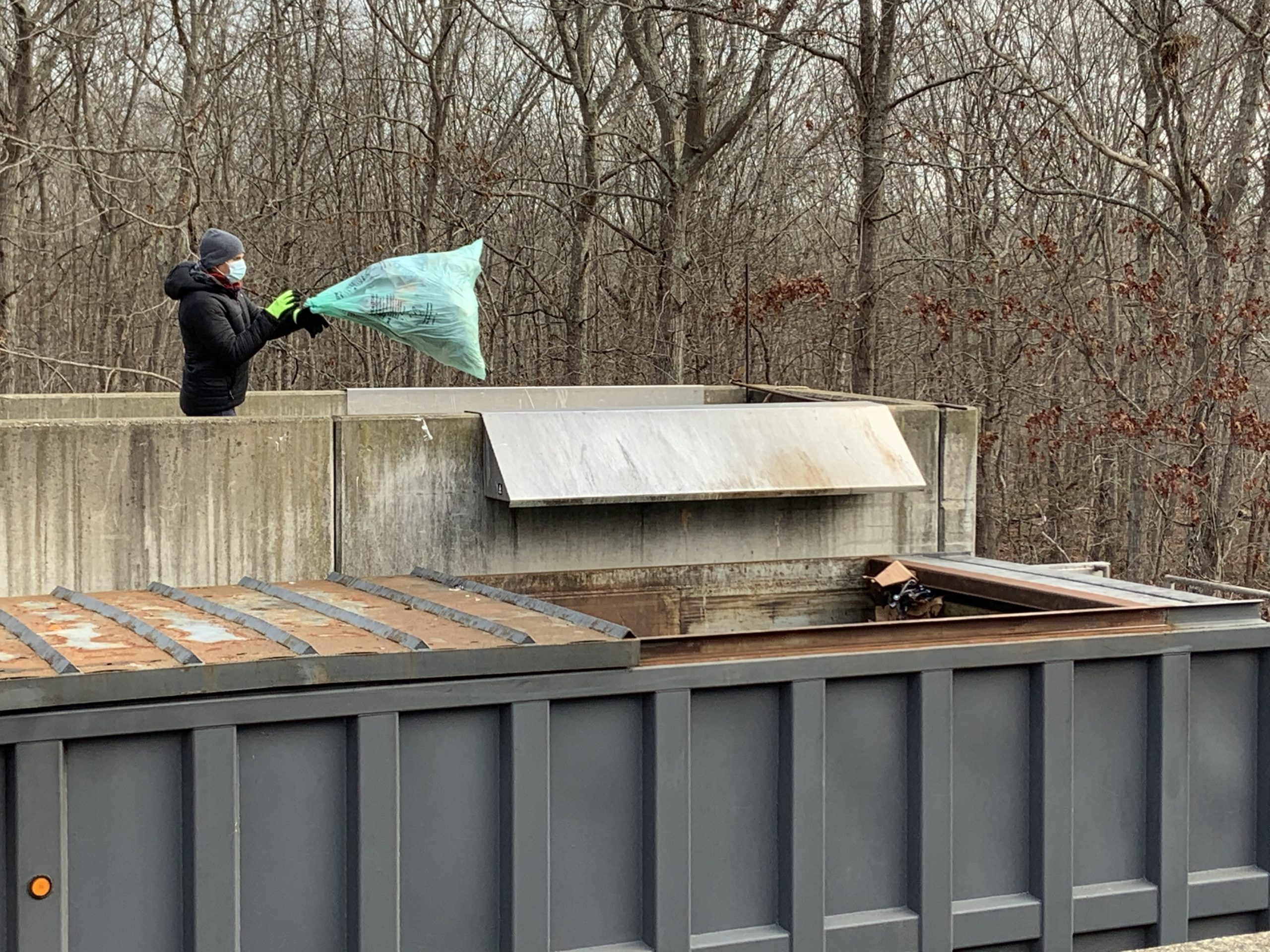 A self-hauler tosses a green bag full of nonrecyclable garbage at the Sag Harbor transfer station. STEPHEN J. KOTZ