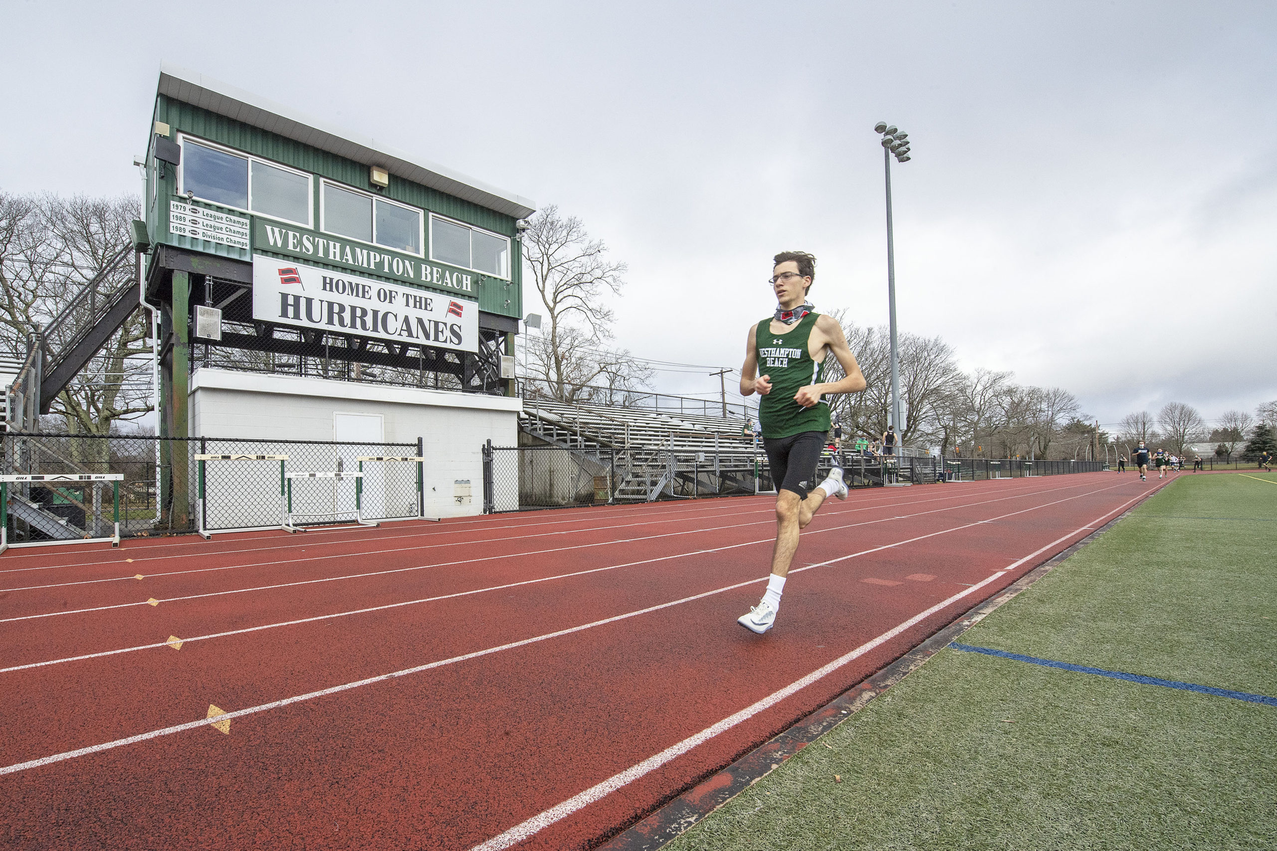 Gavin Ehlers leads the field by a large margin during the 1600 meter race as the Westhampton Beach boys track team competes against the team from Rocky Point at Westhampton Beach High School on Saturday.       MICHAEL HELLER