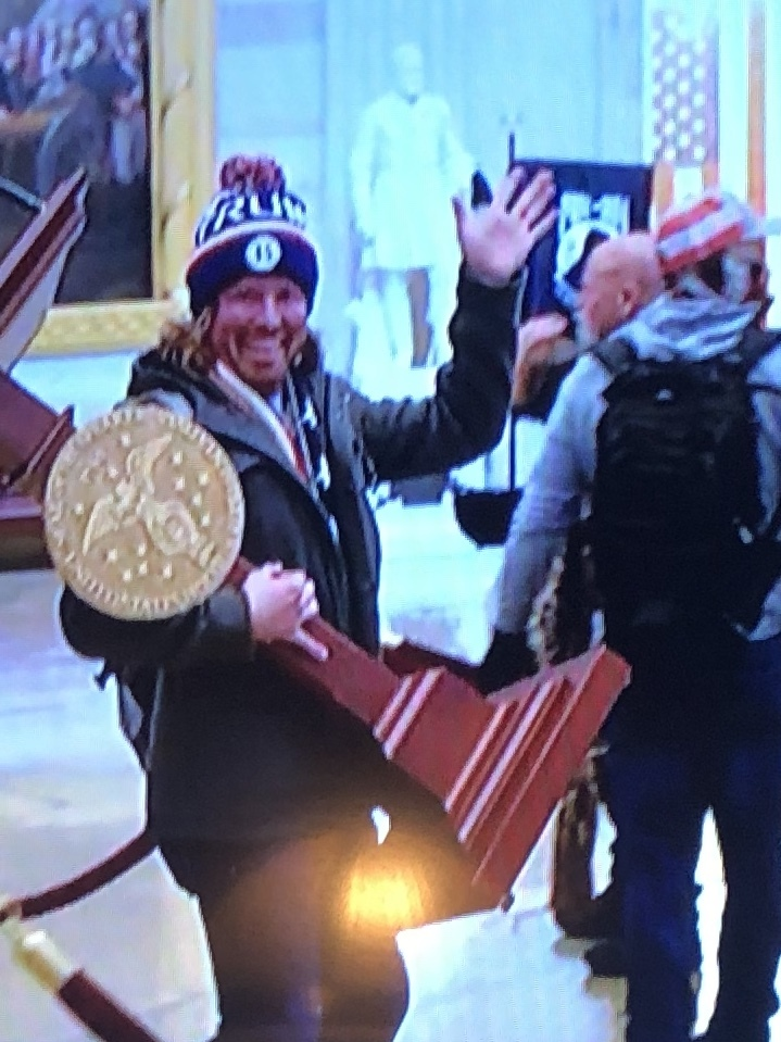 One of the looters with an item taken from the Capitol Building, shown on television Wednesday.