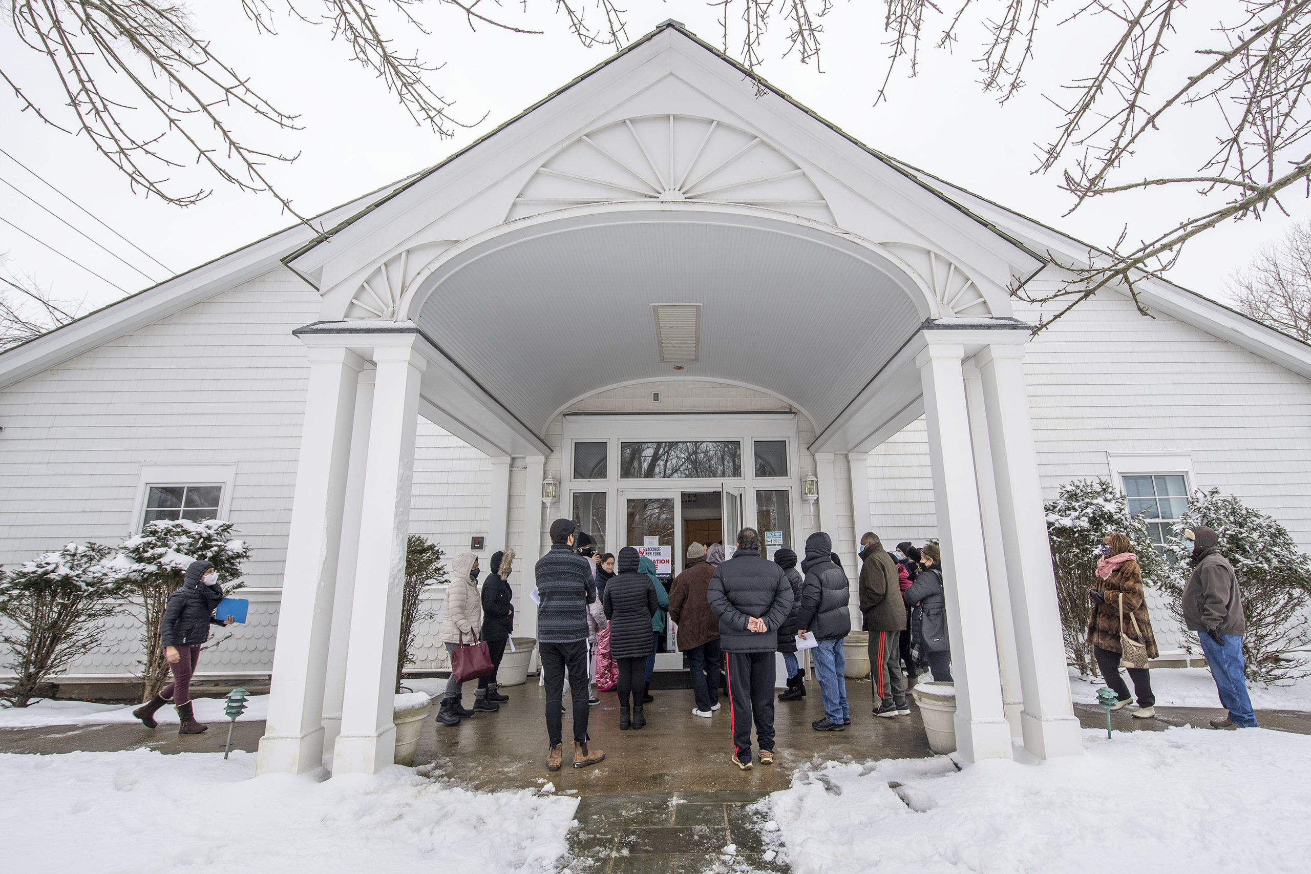 A crowd of people with appointments waits outside the hall during a COVID-19 vaccine POD (Pop Up Dispensary) organized by OLA (Organización Latino-Americana) in the Ryan Dempsey Parrish Hall of the Most Holy Trinity Church in East Hampton on Friday.    MICHAEL HELLER